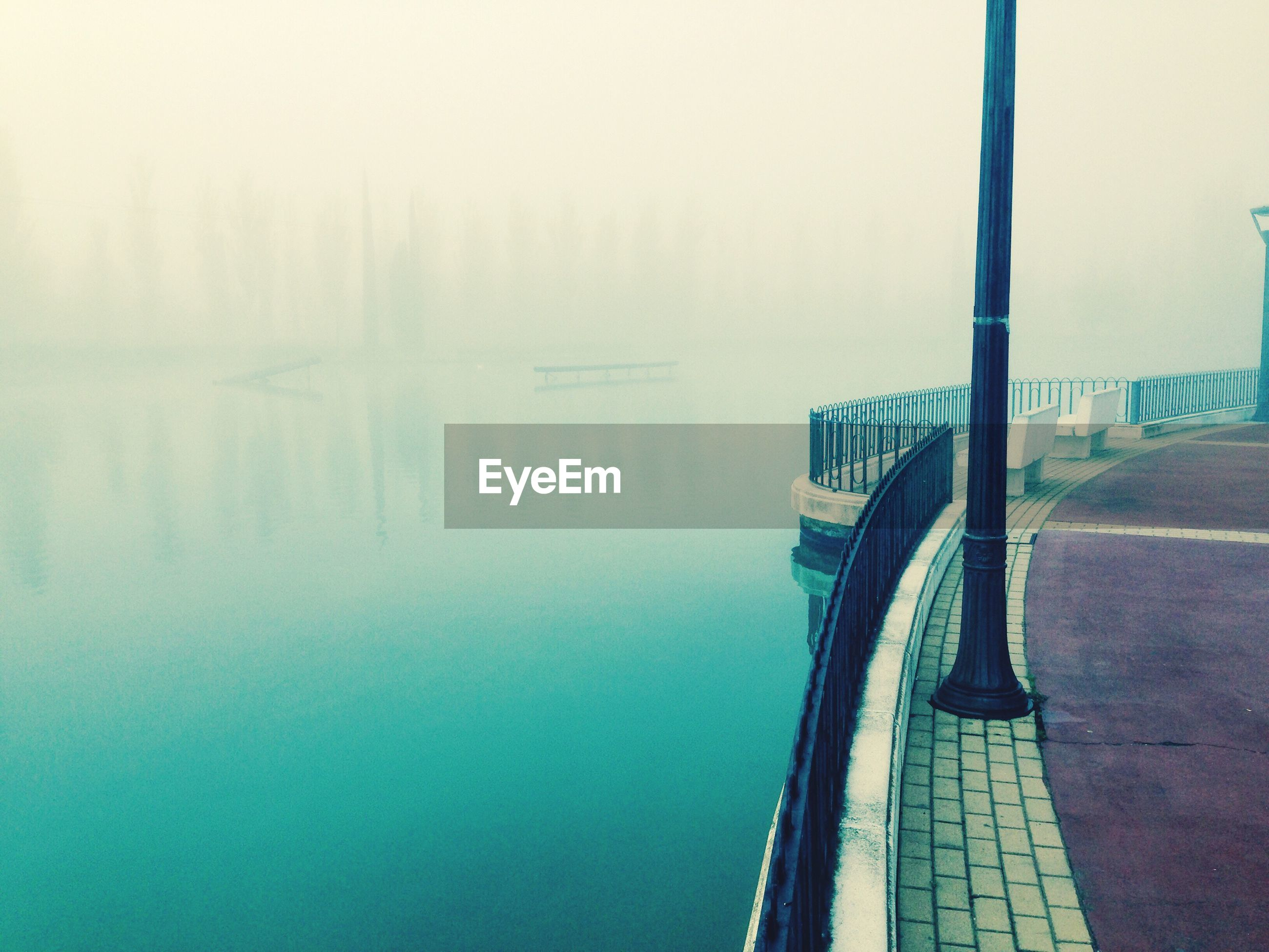 Promenade by calm lake during foggy weather