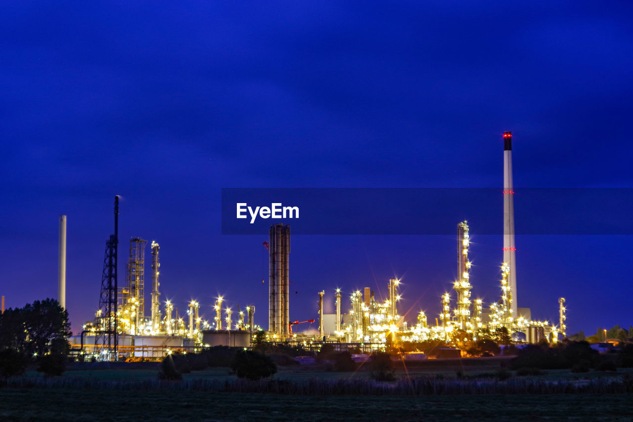 factory, illuminated, fuel and power generation, industry, oil industry, sky, night, nature, built structure, building exterior, architecture, no people, blue, smoke - physical structure, smoke stack, water, outdoors, dusk, refinery, pollution, chemical plant