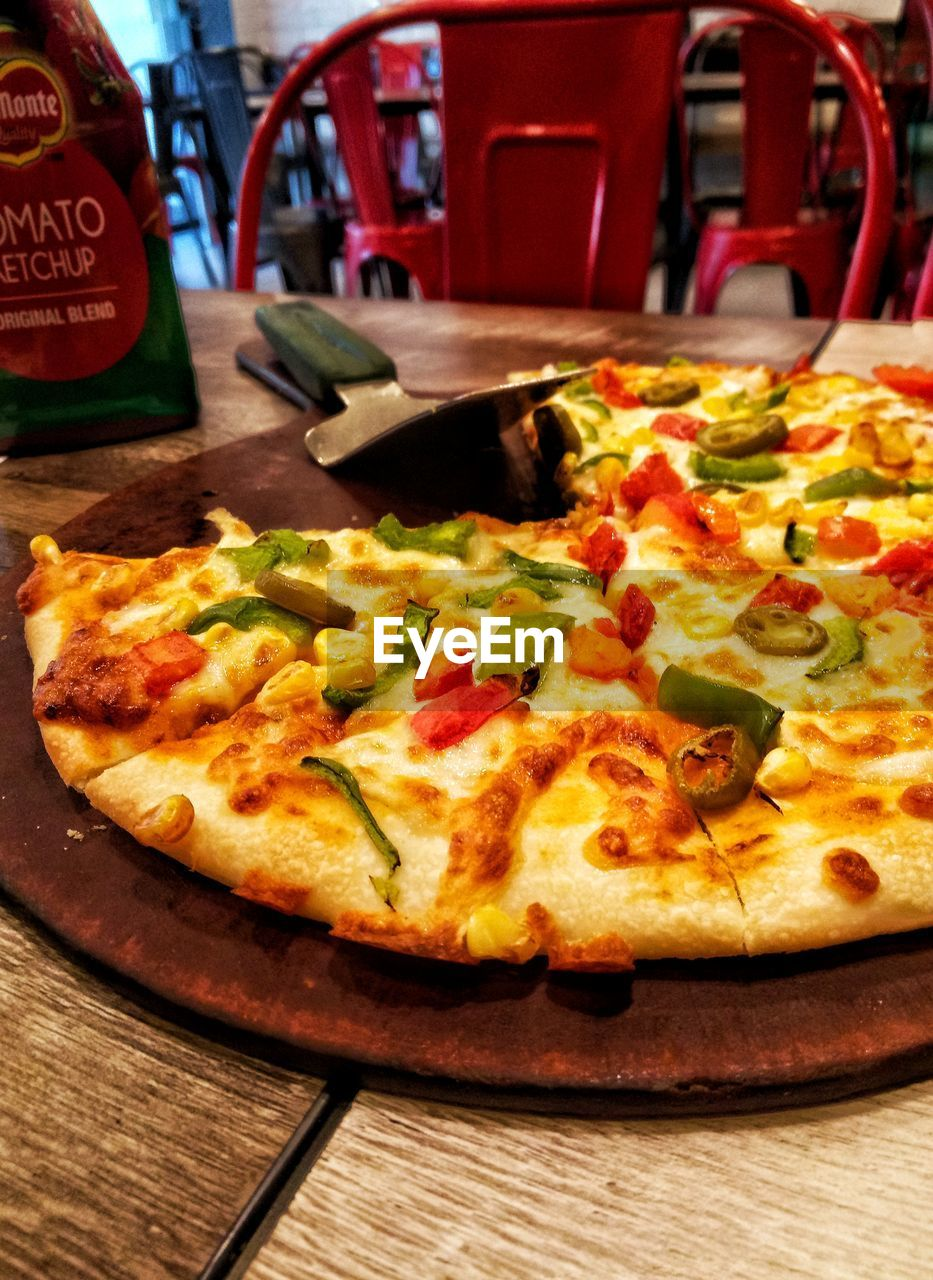 food and drink, pizza, food, table, freshness, ready-to-eat, indoors, close-up, still life, cheese, dairy product, unhealthy eating, vegetable, no people, wood - material, restaurant, italian food, focus on foreground, fast food, snack, vegetarian food, pizzeria, temptation