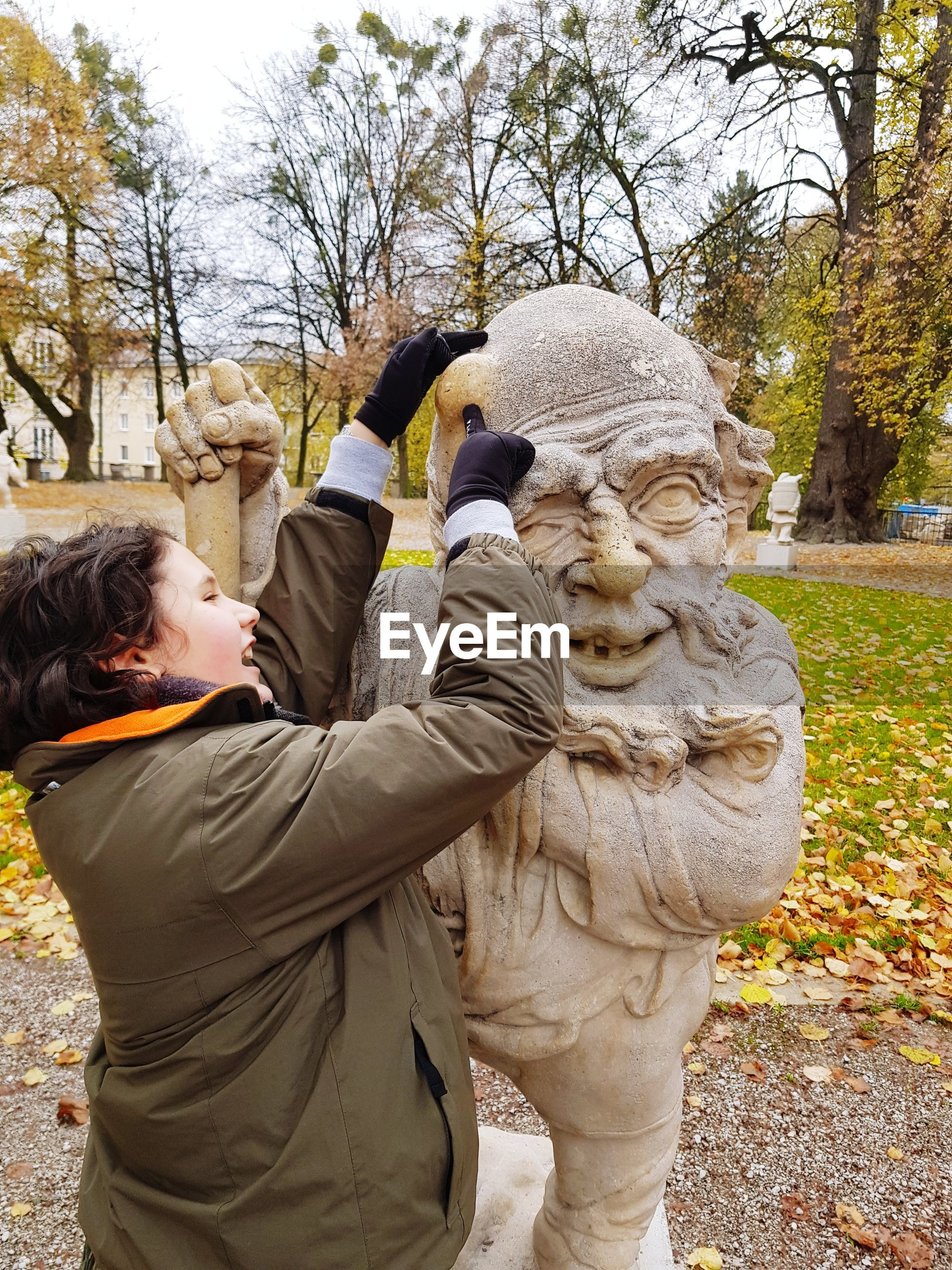Boy touching sculpture in park