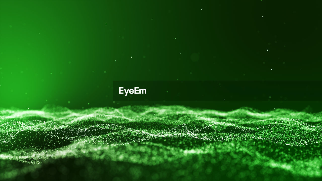 Abstract image of glittering particles against green background