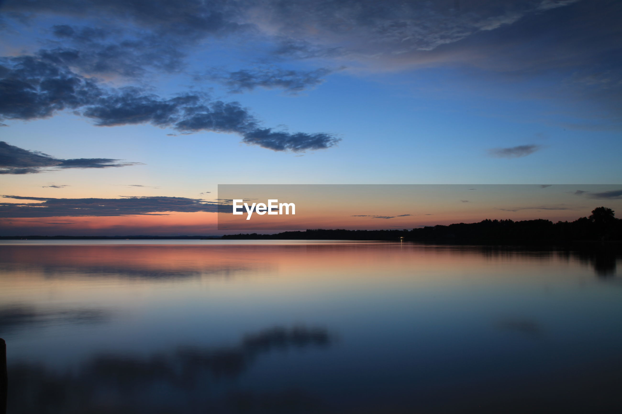 Scenic view of lake against blue sky at sunset