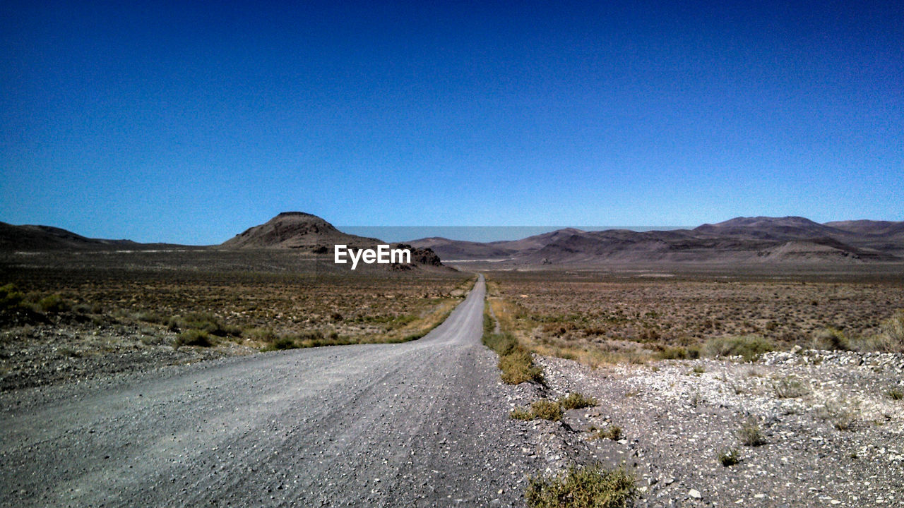 road, landscape, mountain, the way forward, nature, scenics, desert, transportation, mountain range, blue, highway, clear sky, barren, arid climate, empty, remote, asphalt, outdoors, day, tranquil scene, no people, winding road, beauty in nature, sky