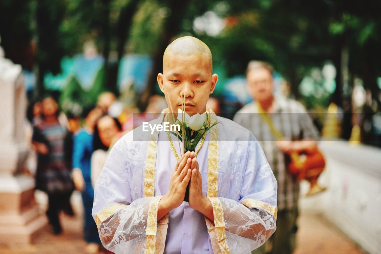 Portrait Of Monk Holding Flowers While Praying