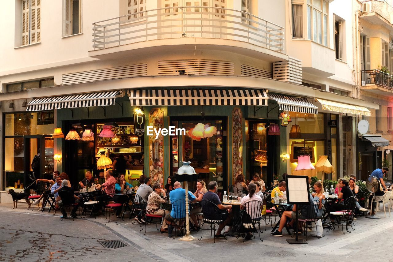 architecture, building exterior, sidewalk cafe, restaurant, built structure, chair, table, cafe, large group of people, sitting, outdoors, men, group of people, city, awning, women, real people, day, people, adult, adults only