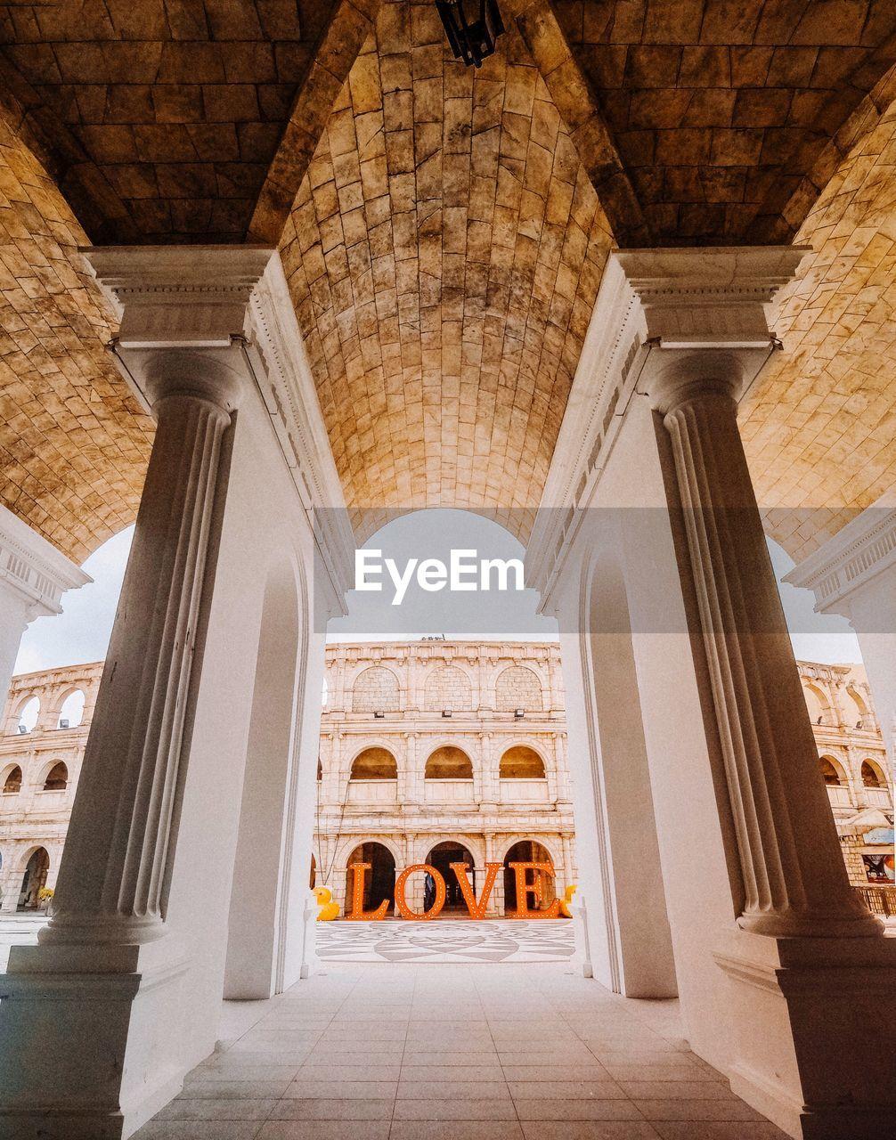 Love Text Against Building Seen Through Columns