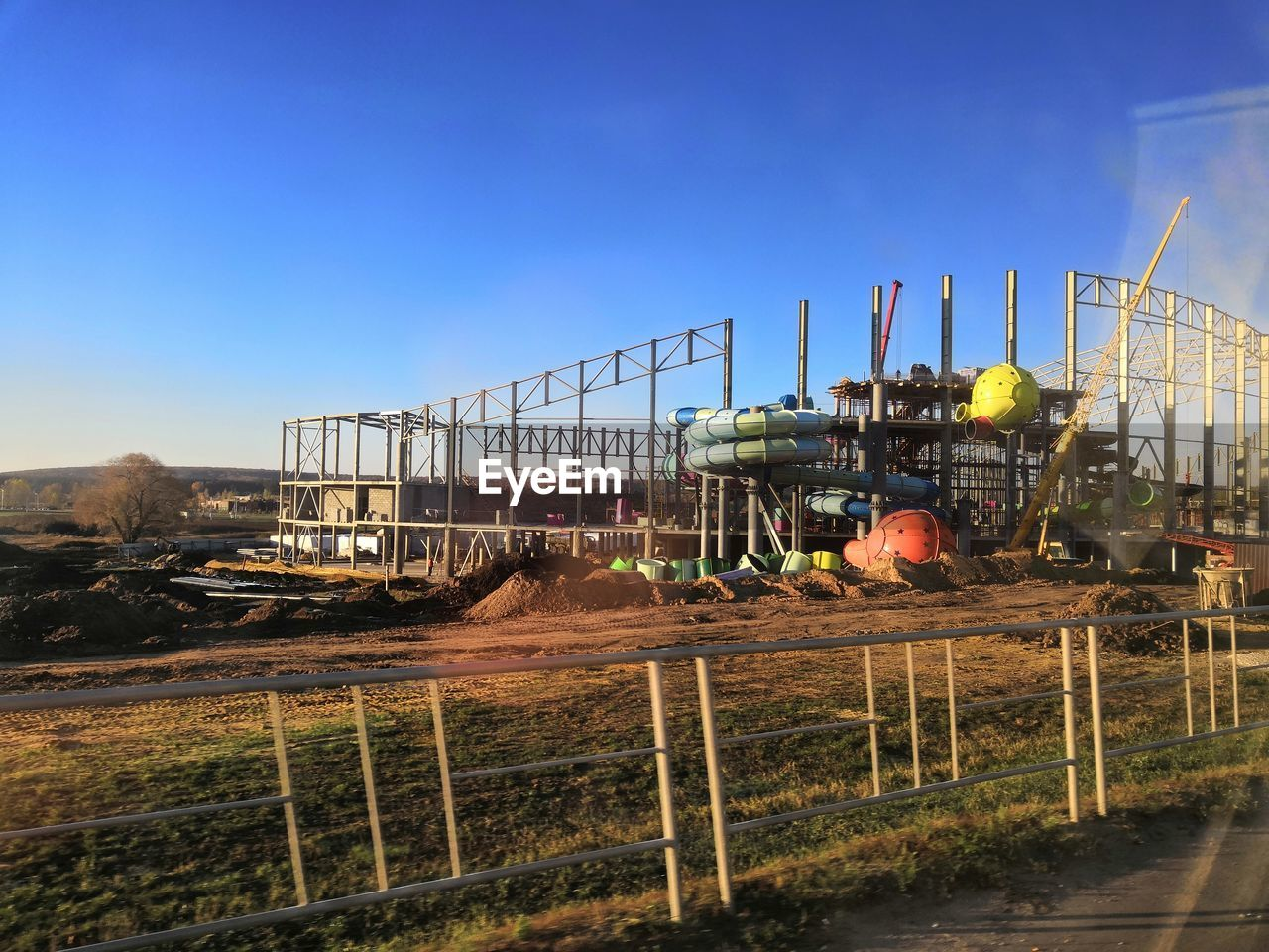 sky, industry, construction industry, nature, construction site, no people, day, clear sky, architecture, machinery, development, blue, outdoors, copy space, fence, built structure, sunlight, factory, incomplete, barrier, industrial equipment, construction equipment