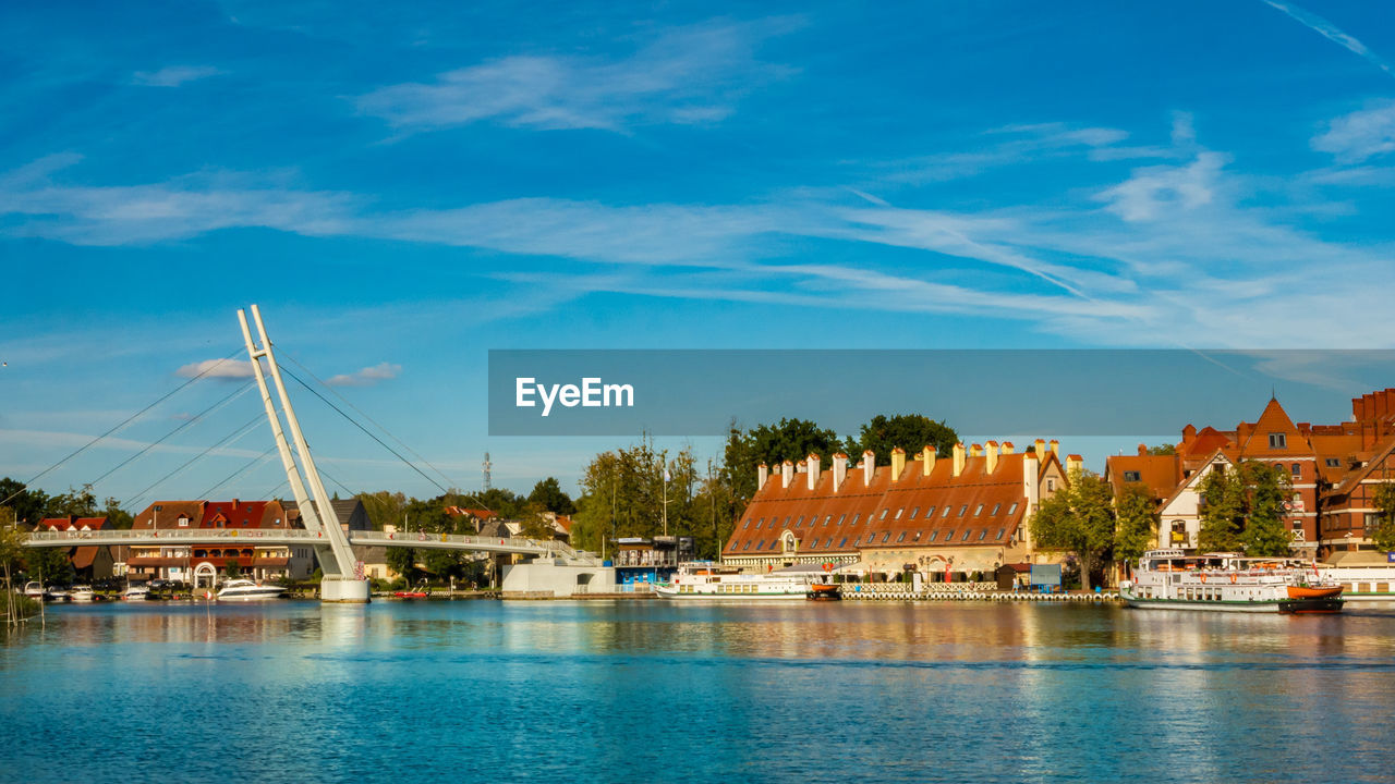 water, built structure, architecture, building exterior, sky, waterfront, transportation, nature, reflection, cloud - sky, tree, building, day, travel destinations, city, blue, river, no people, bridge, bridge - man made structure, outdoors, swimming pool