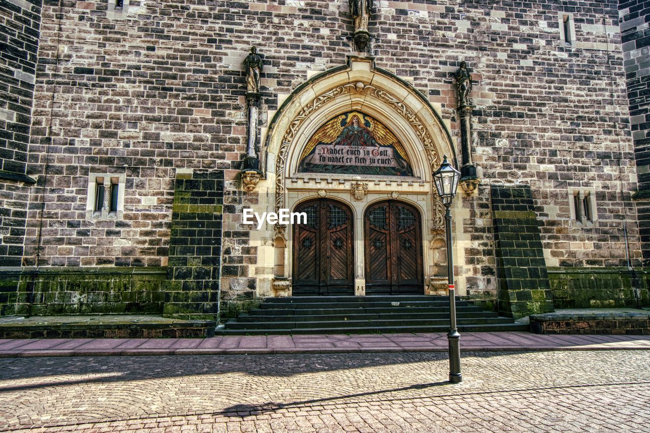 building exterior, architecture, built structure, building, arch, entrance, door, no people, facade, brick, place of worship, the past, day, history, brick wall, wall, city, religion, window, outdoors