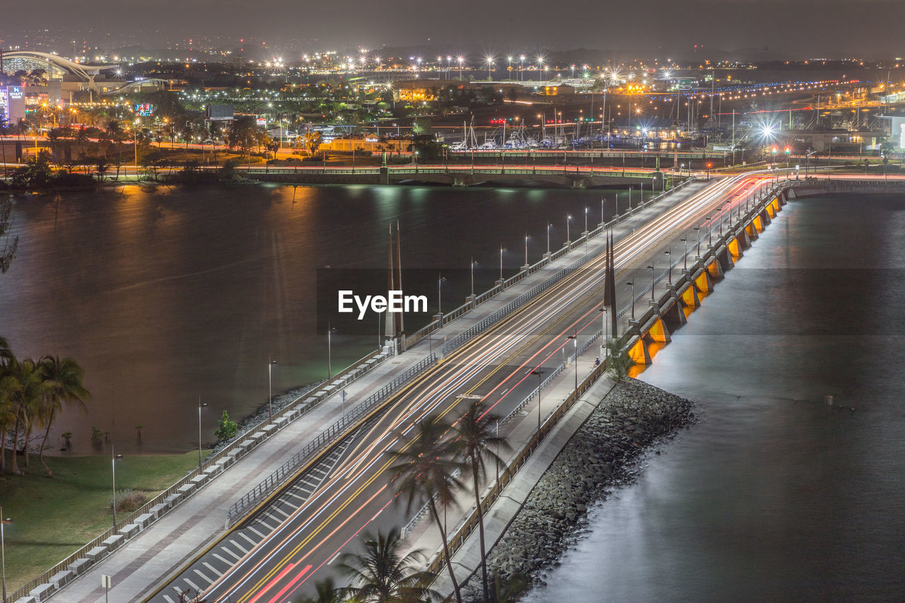 architecture, water, built structure, river, long exposure, bridge - man made structure, motion, city, illuminated, connection, building exterior, light trail, transportation, speed, high angle view, no people, road, outdoors, night, bridge, urban scene, chain bridge, high street, cityscape, sky
