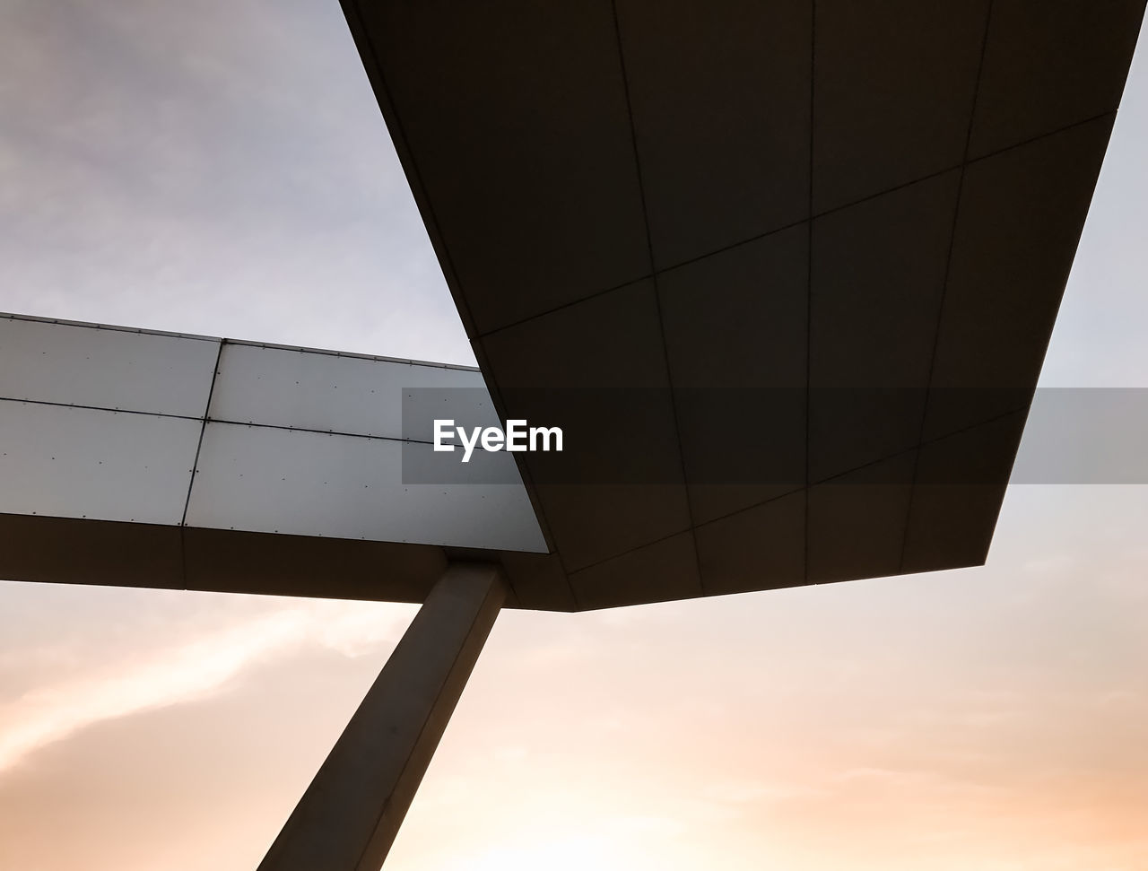 Low Angle View Of Built Structure Against Cloudy Sky During Sunset