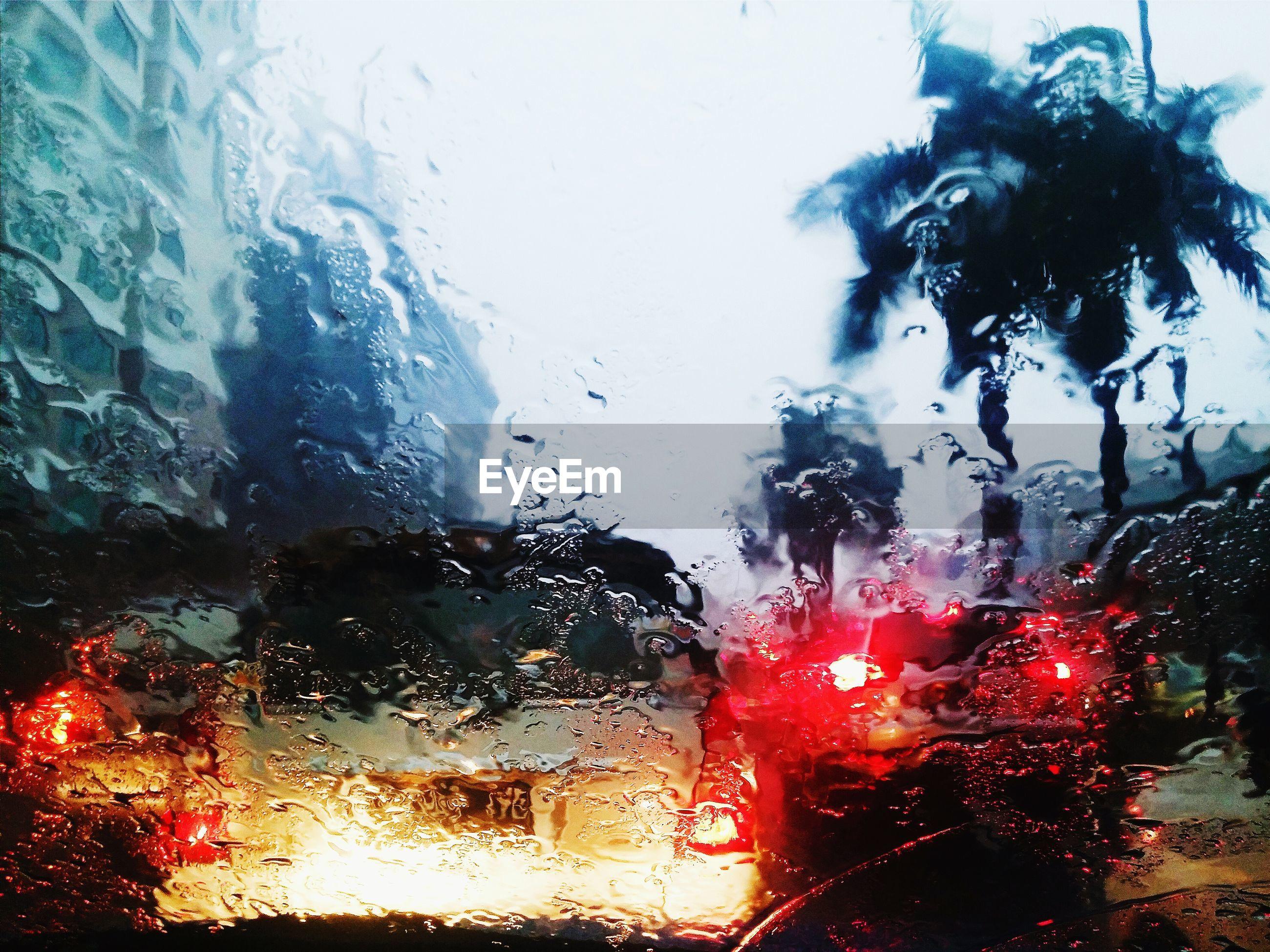 Car seen through wet windshield
