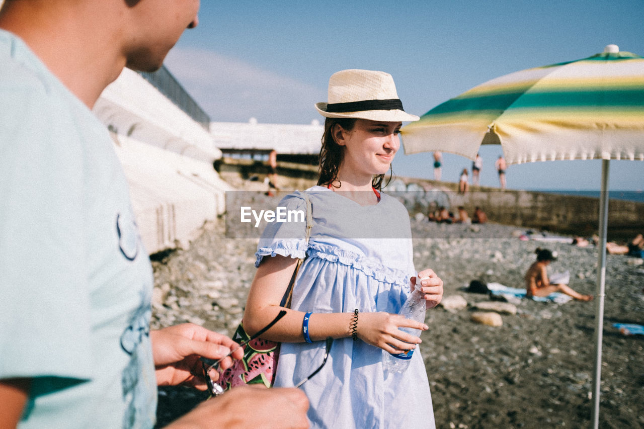 Midsection of man with woman standing at beach during sunny day