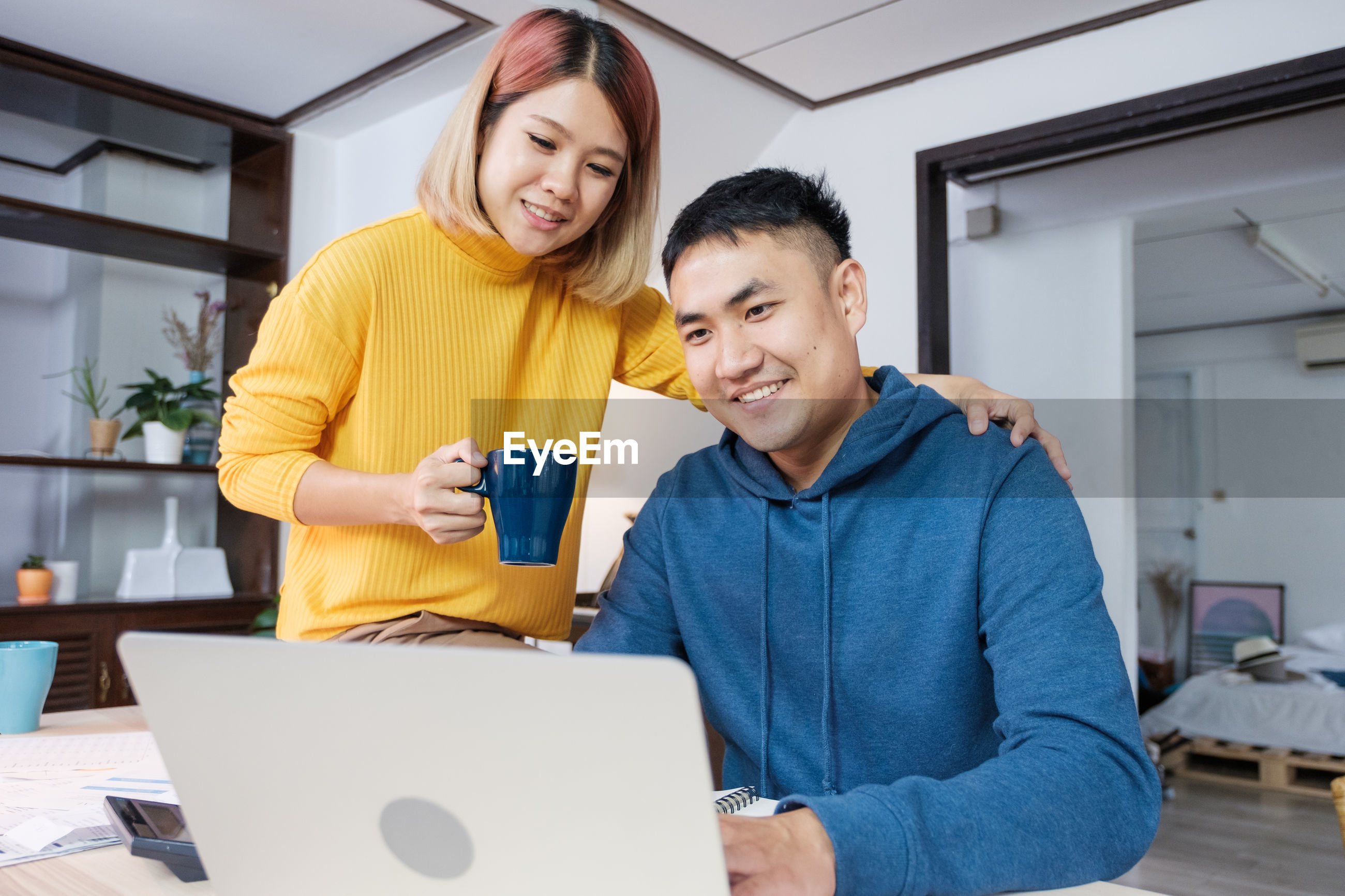 Young man with woman using laptop at home