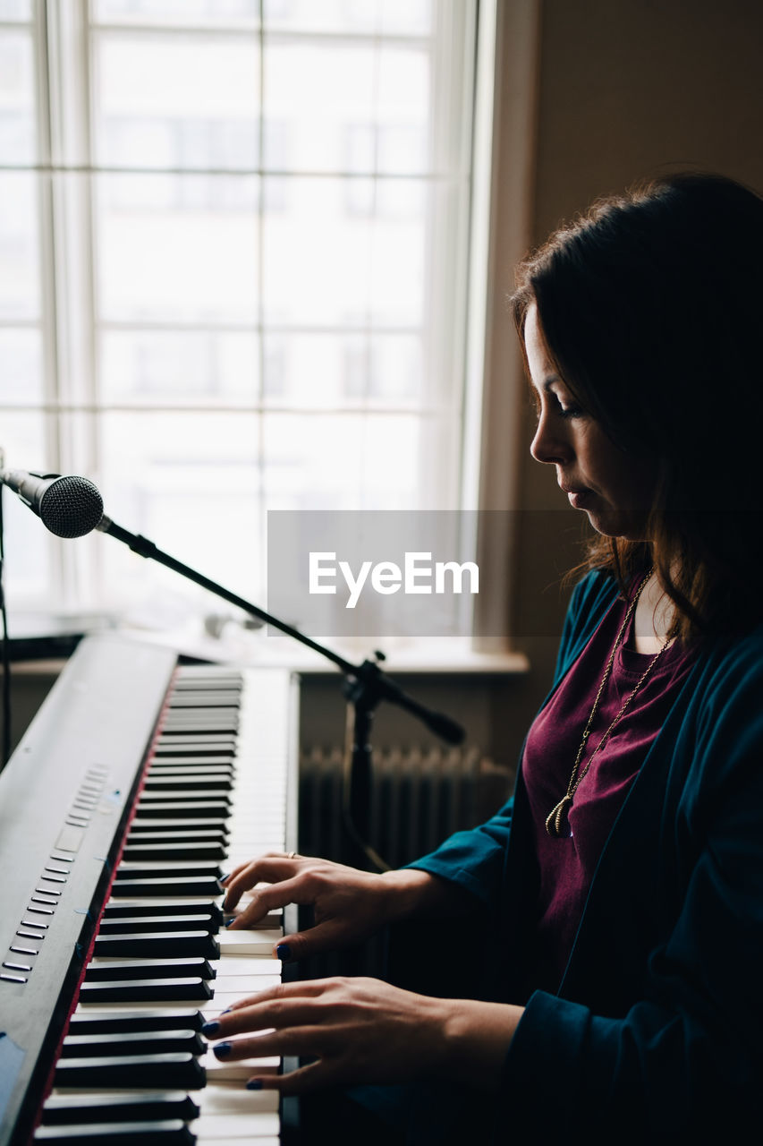 musical equipment, musical instrument, piano, music, arts culture and entertainment, musician, indoors, side view, playing, one person, sitting, skill, leisure activity, real people, pianist, lifestyles, women, practicing, concentration, piano key, keyboard, keyboard instrument