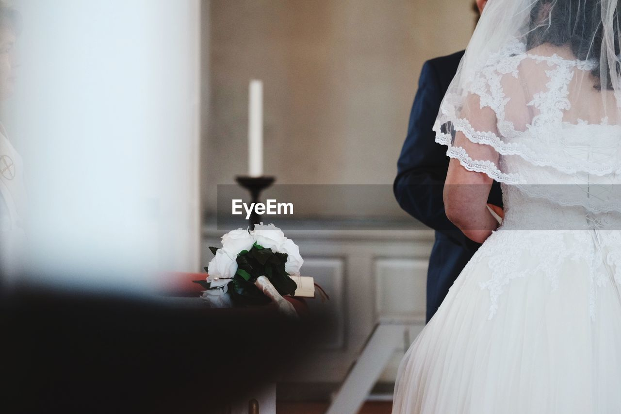 Midsection of couple standing in church during wedding ceremony