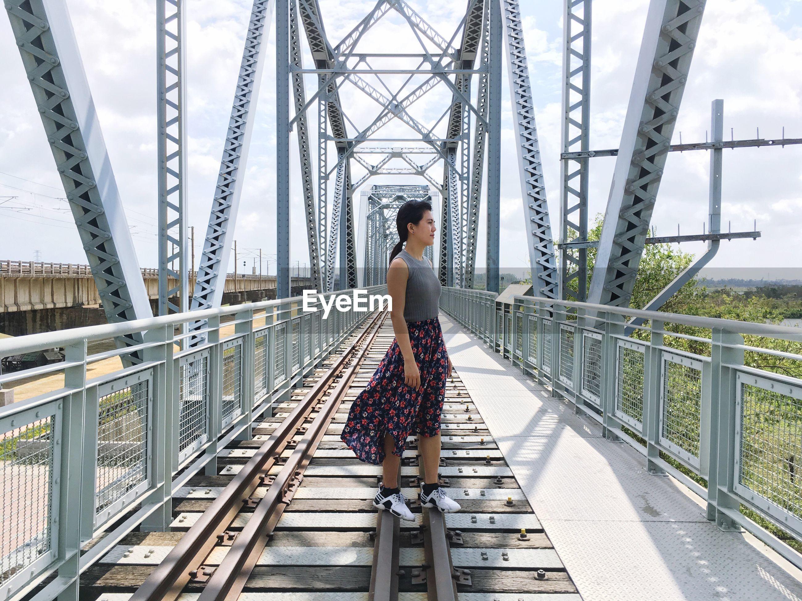 Young woman standing on railway bridge