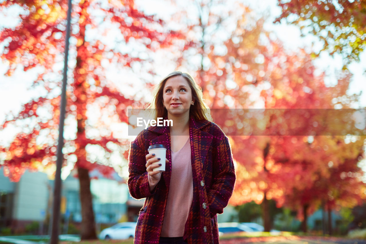Young Woman Holding Coffee While Standing Against Autumn Trees