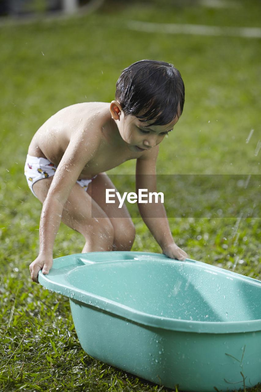 Shirtless Boy Holding Bathtub In Lawn
