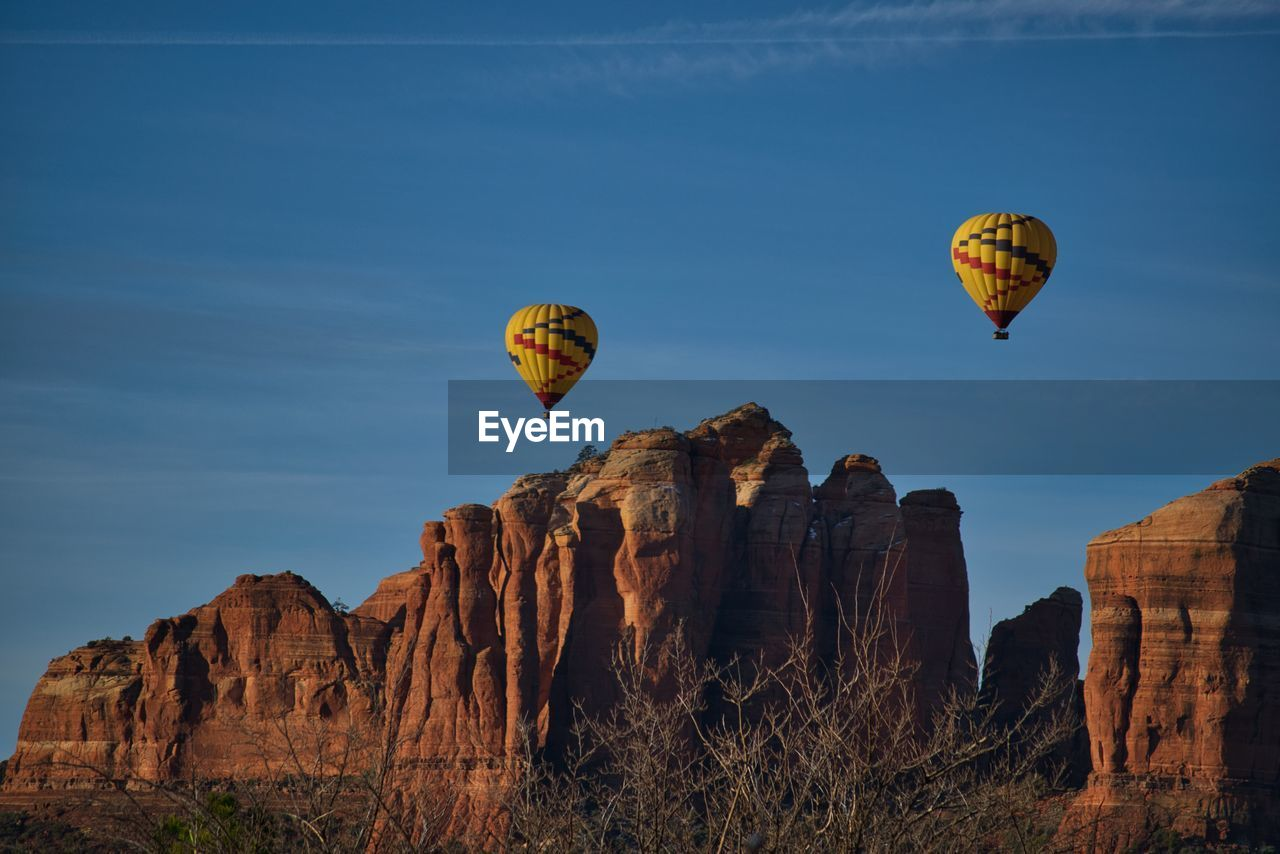 rock formation, rock, sky, adventure, solid, nature, hot air balloon, beauty in nature, transportation, rock - object, flying, air vehicle, travel, mountain, scenics - nature, mid-air, balloon, non-urban scene, travel destinations, day, no people, outdoors, formation, ballooning festival