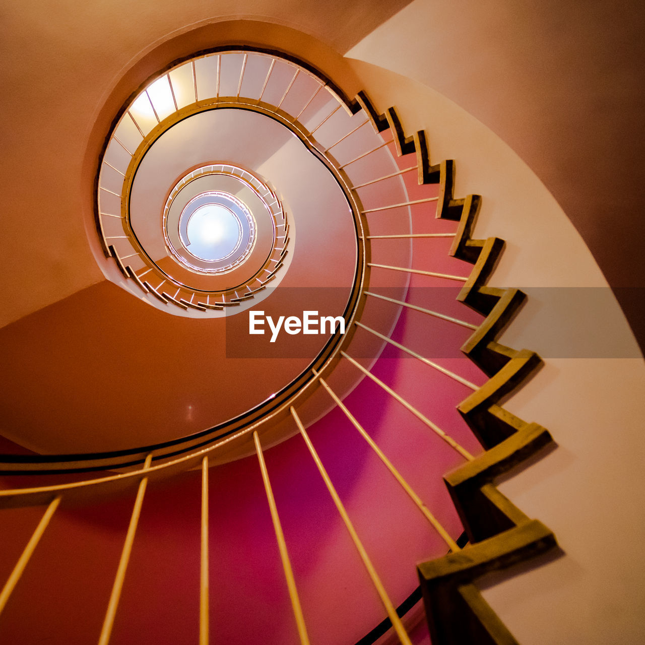 steps and staircases, staircase, spiral, railing, indoors, spiral staircase, architecture, built structure, pattern, illuminated, no people, design, shape, directly below, low angle view, building, lighting equipment, geometric shape, diminishing perspective, ceiling
