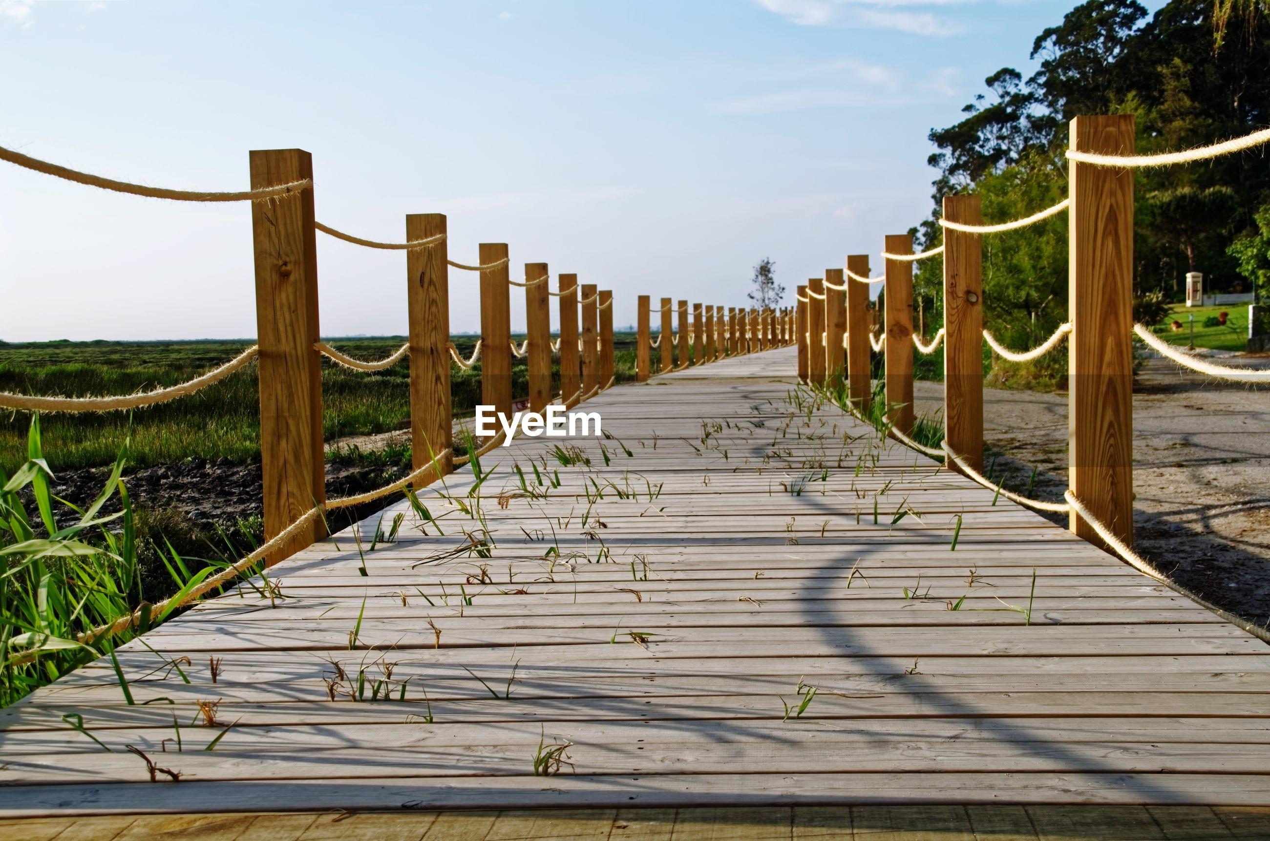 Wooden boardwalk leading towards gazebo against sky