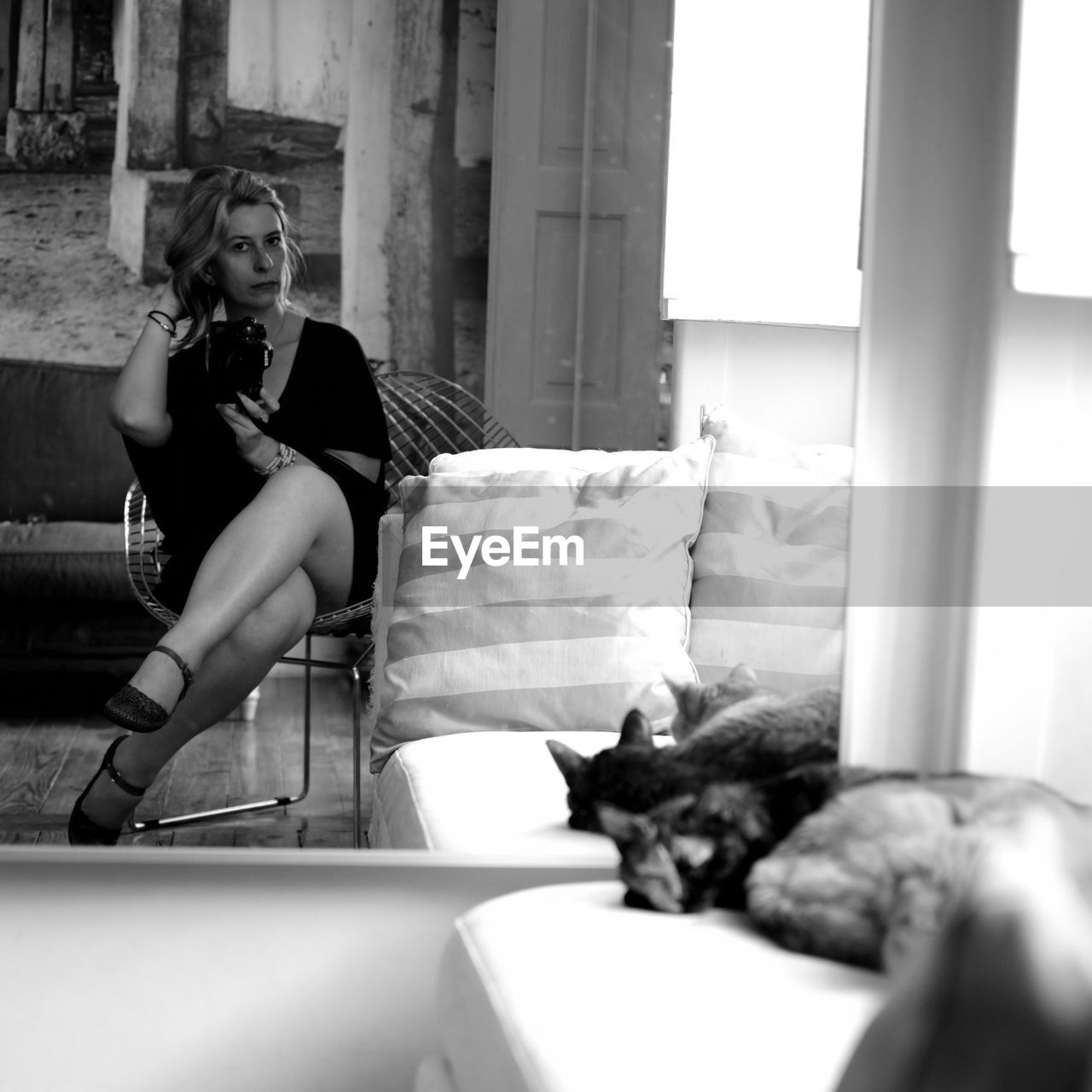 Woman Photographing With Camera While Reflecting On Mirror At Home