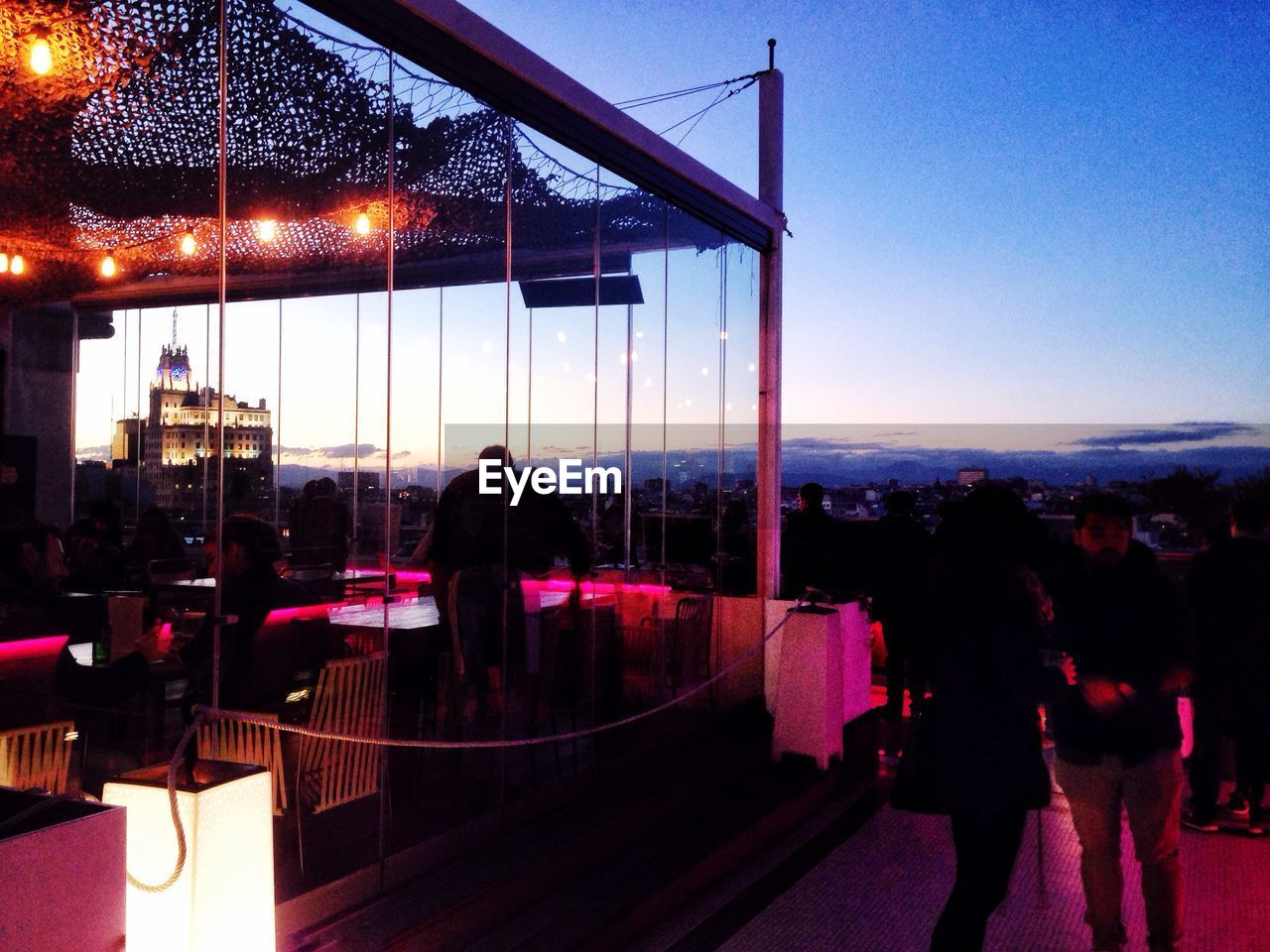People On Restaurant Terrace Against Sky At Dusk