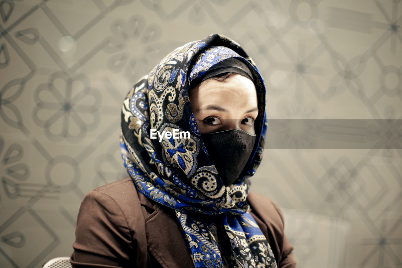 Portrait of woman wearing mask against wall