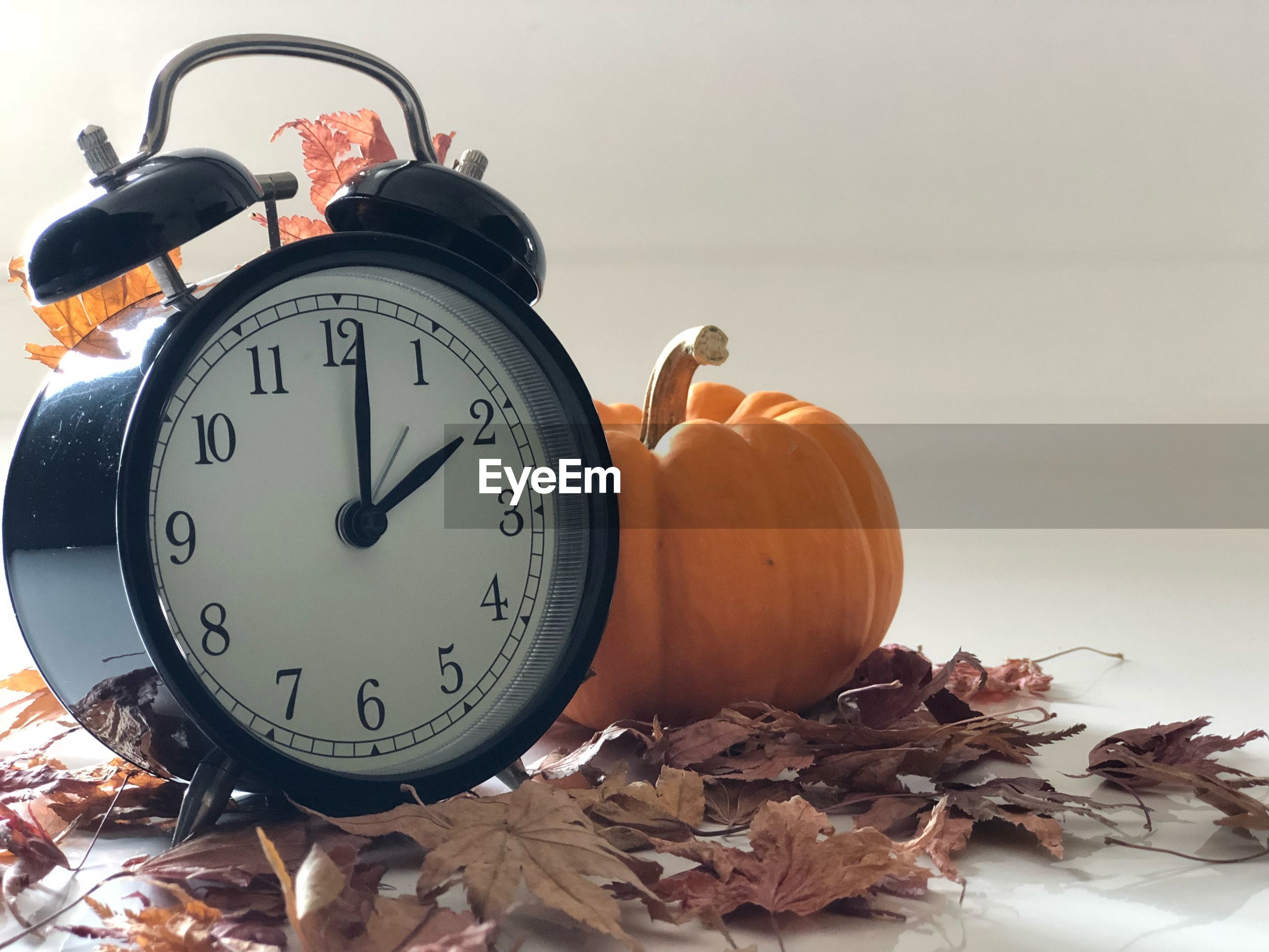 Close-up of alarm clock by pumpkin and dry leaves on table
