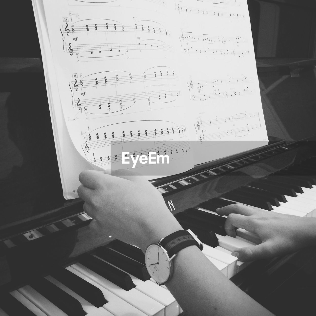 Cropped image of person holding music sheet while playing piano