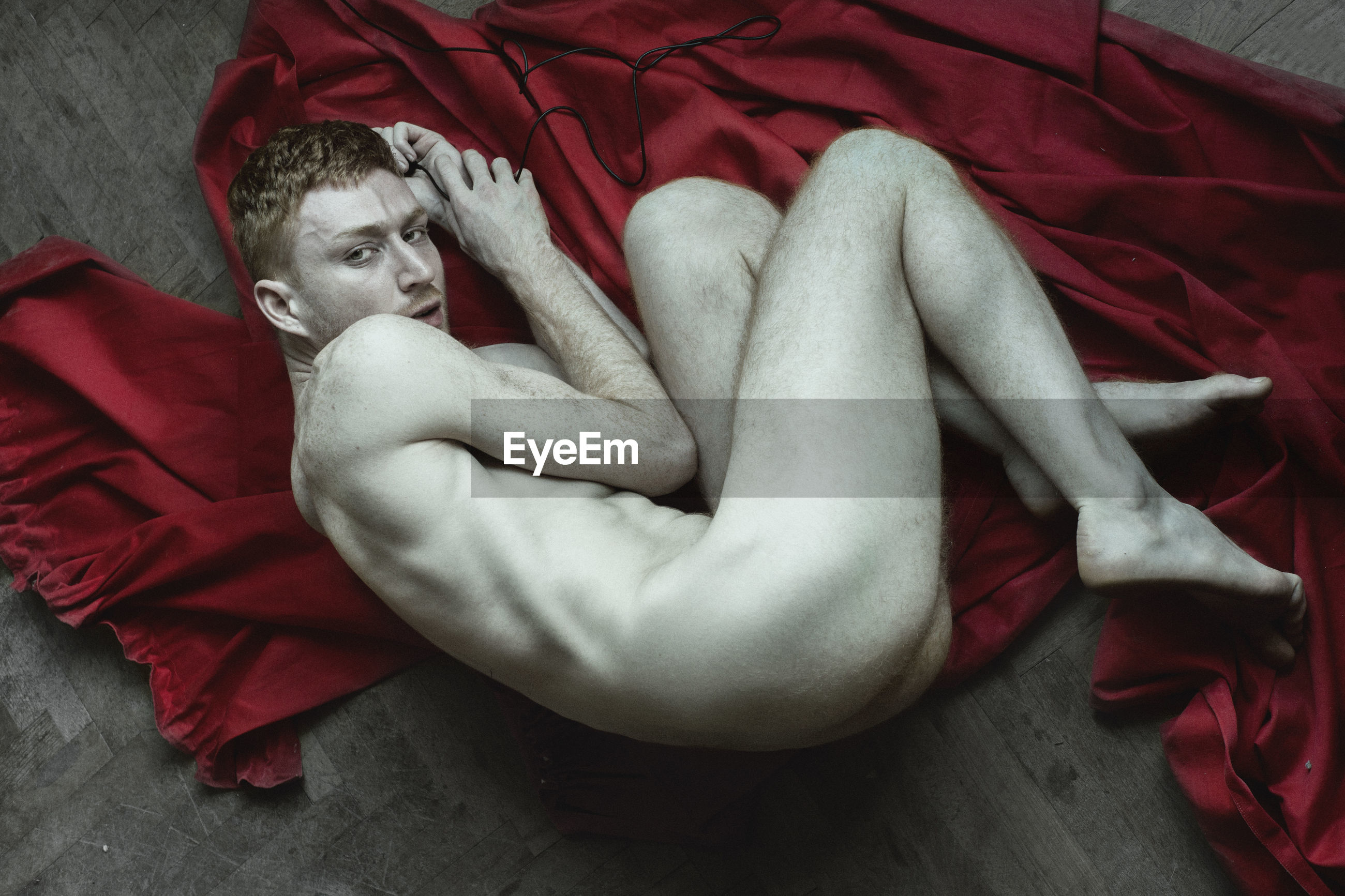 High angle portrait of naked man lying on red fabric