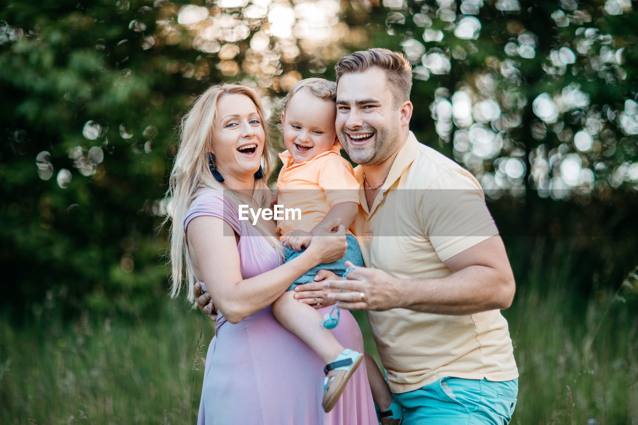 Happy Pregnant Woman With Family Standing On Field At Park