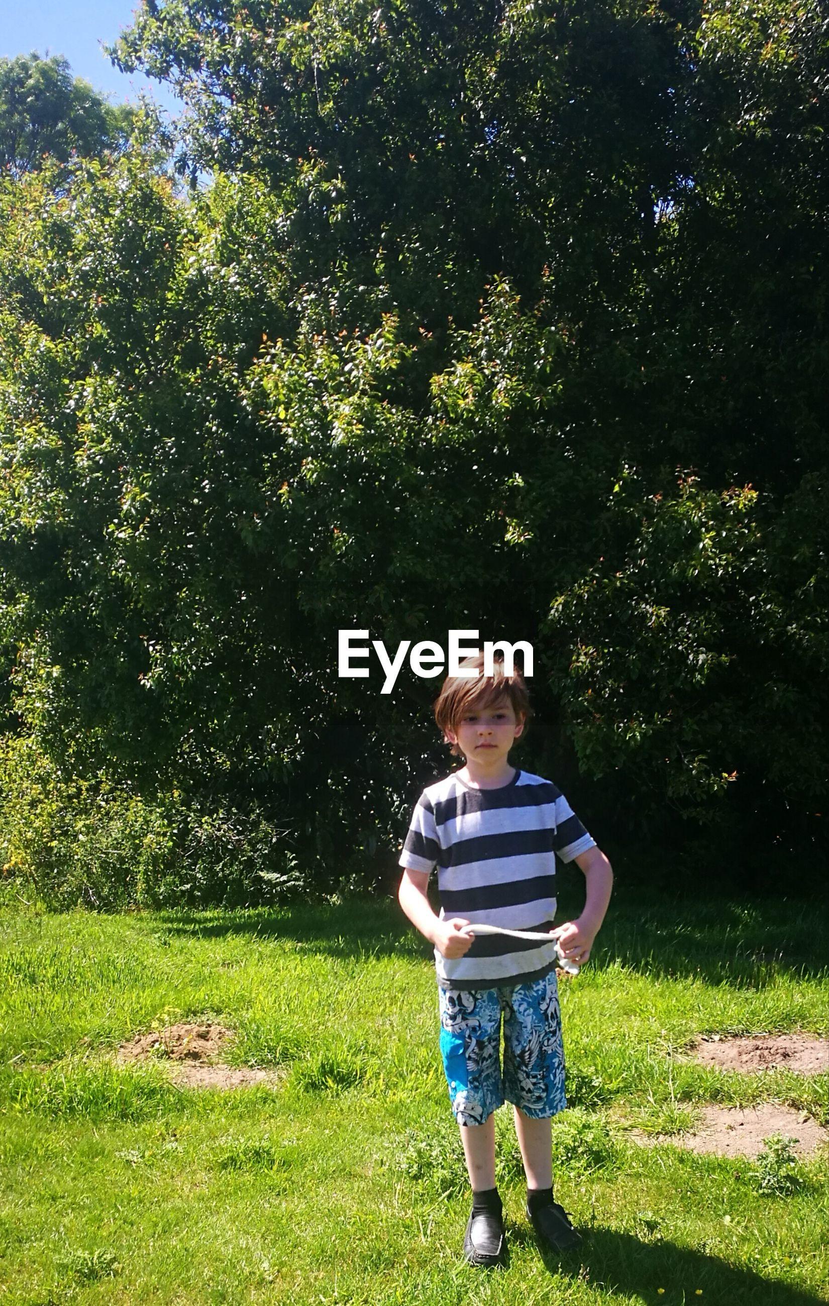 Full length of boy standing on grassy field against trees