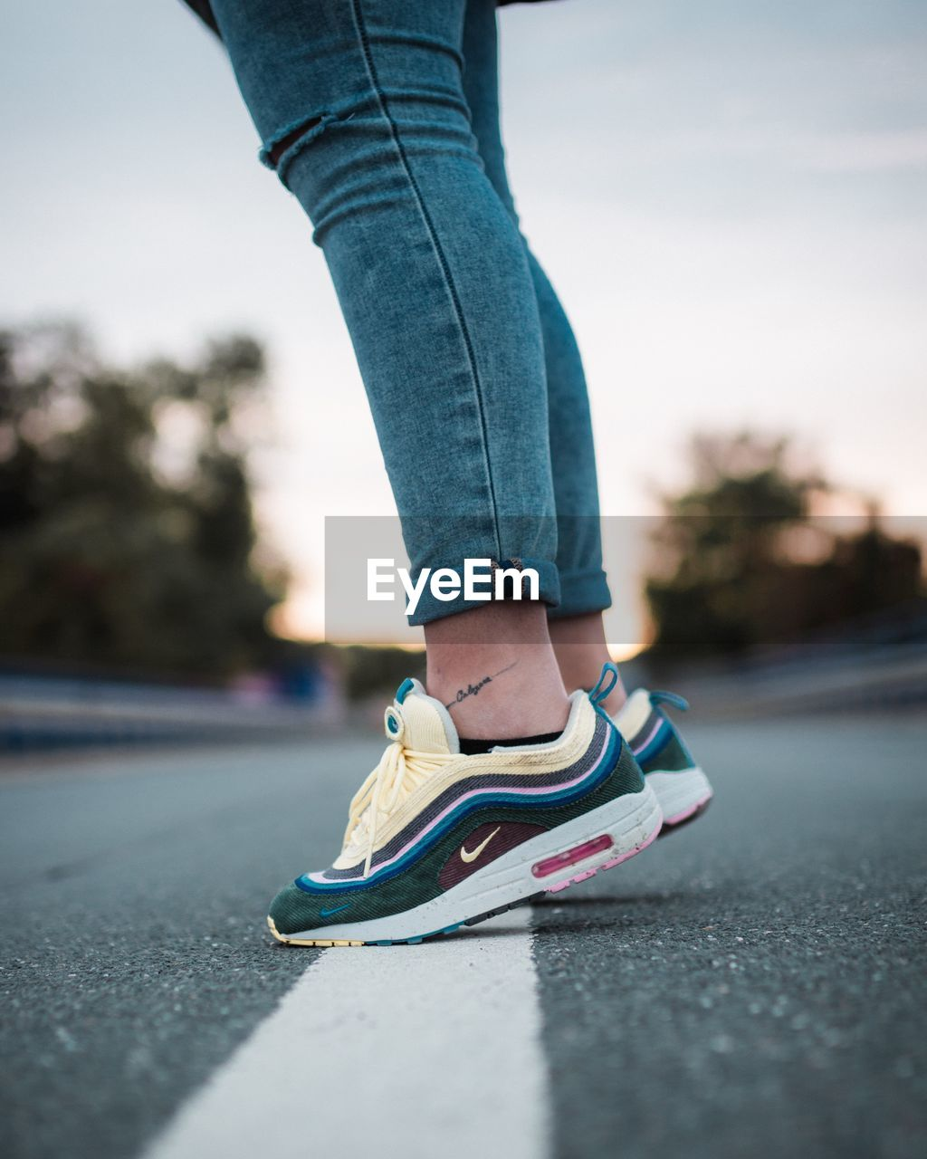 shoe, one person, low section, human leg, jeans, lifestyles, city, human body part, body part, road, casual clothing, real people, street, transportation, day, women, leisure activity, focus on foreground, skateboard, outdoors, human foot, human limb