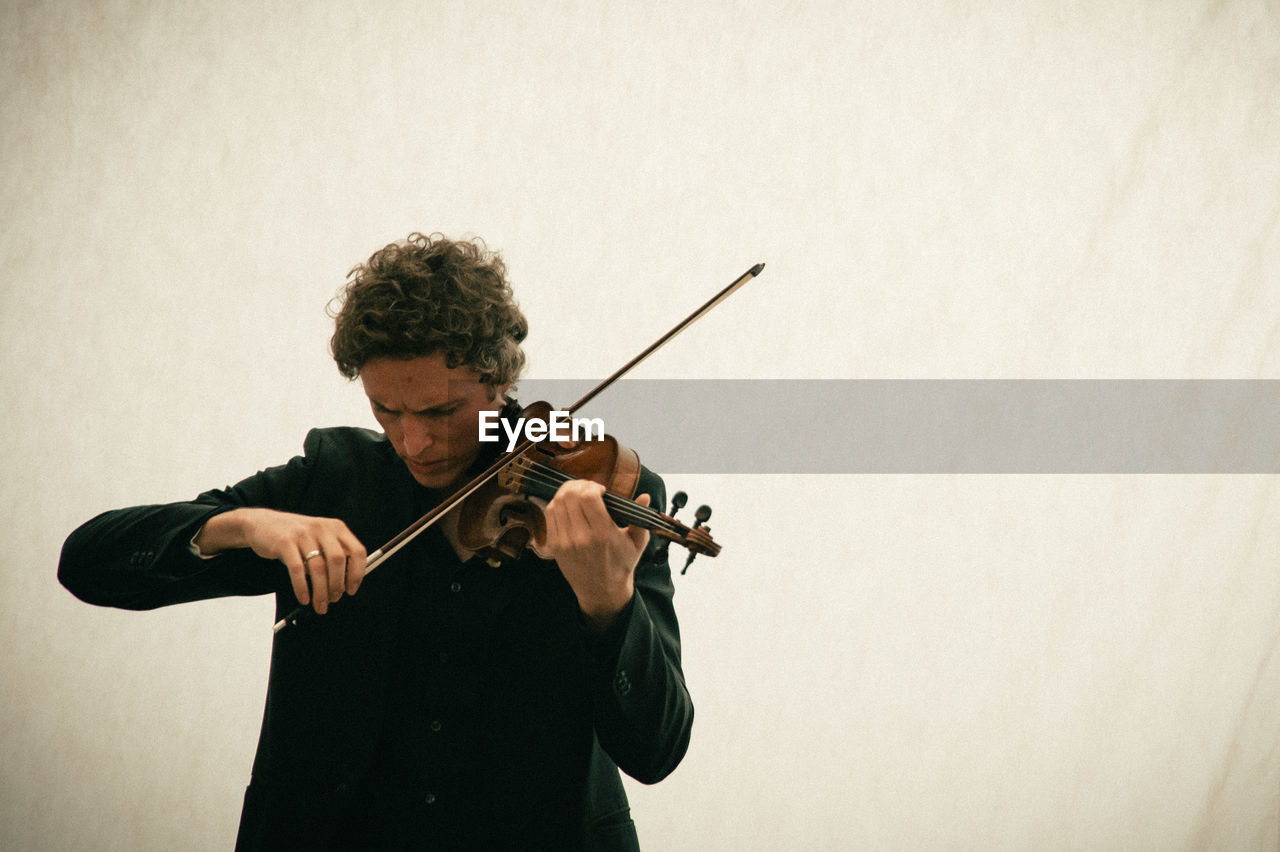 Man Playing Violin While Standing Against Wall
