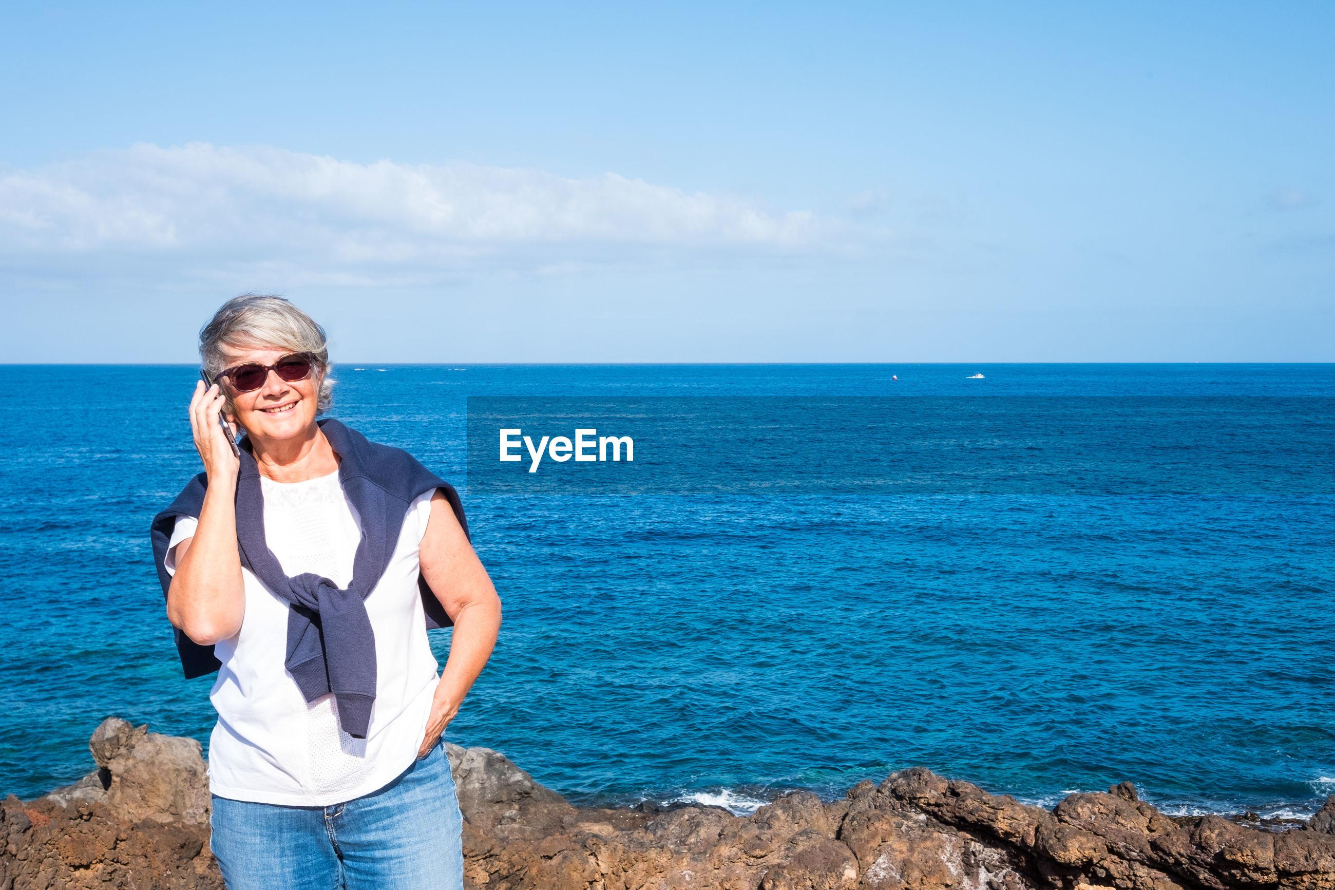 Senior woman standing against sea