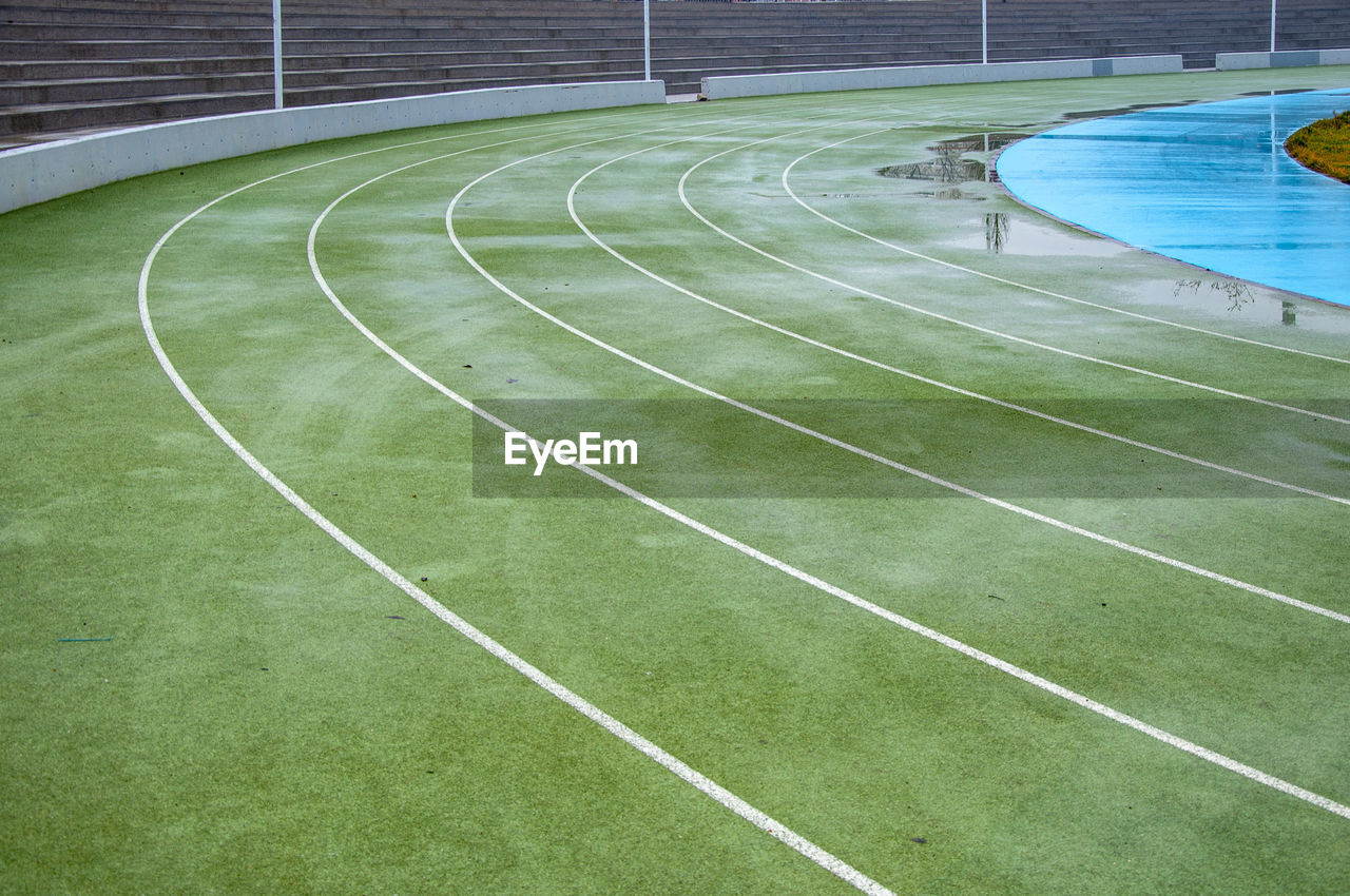 sport, absence, grass, green color, no people, stadium, day, empty, plant, curve, outdoors, nature, competition, high angle view, competitive sport, copy space, track and field, sports track, team sport, playing field