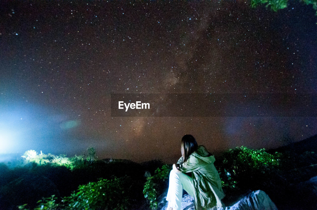 Rear View Of Woman Sitting Against Star Field At Night