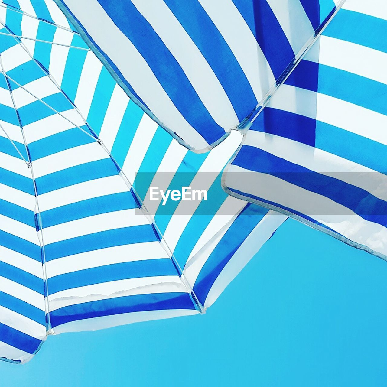 blue, striped, protection, low angle view, shelter, weather, full frame, wet, day, outdoors, no people, backgrounds, clear sky, sky, close-up, under