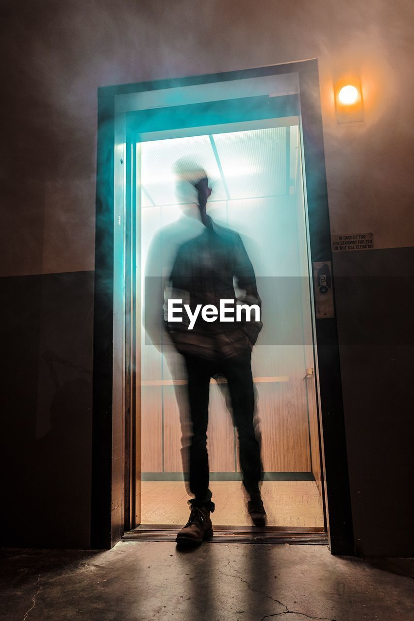 one person, real people, men, blurred motion, indoors, full length, standing, door, entrance, rear view, illuminated, lifestyles, transparent, motion, wall - building feature, architecture, adult, occupation, glass - material, digital composite