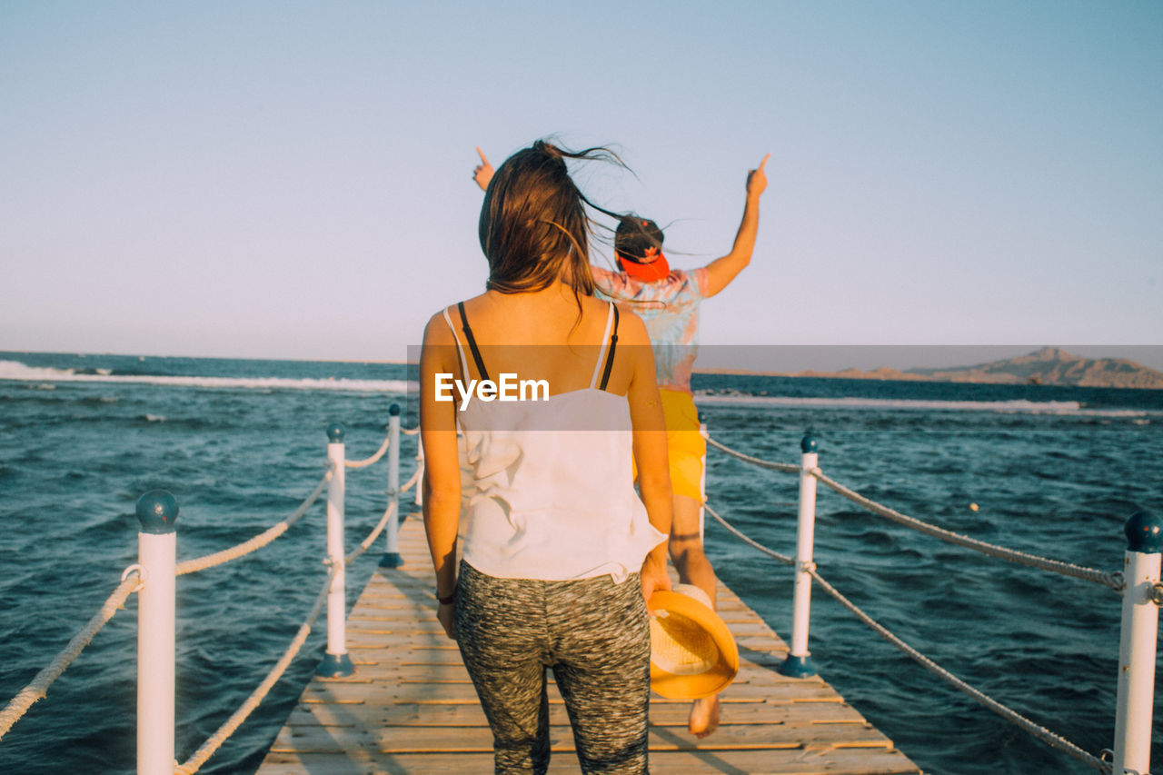 sea, real people, one person, rear view, standing, water, leisure activity, railing, outdoors, horizon over water, clear sky, lifestyles, nature, day, beauty in nature, sky, weekend activities, women, scenics, nautical vessel, young adult, people