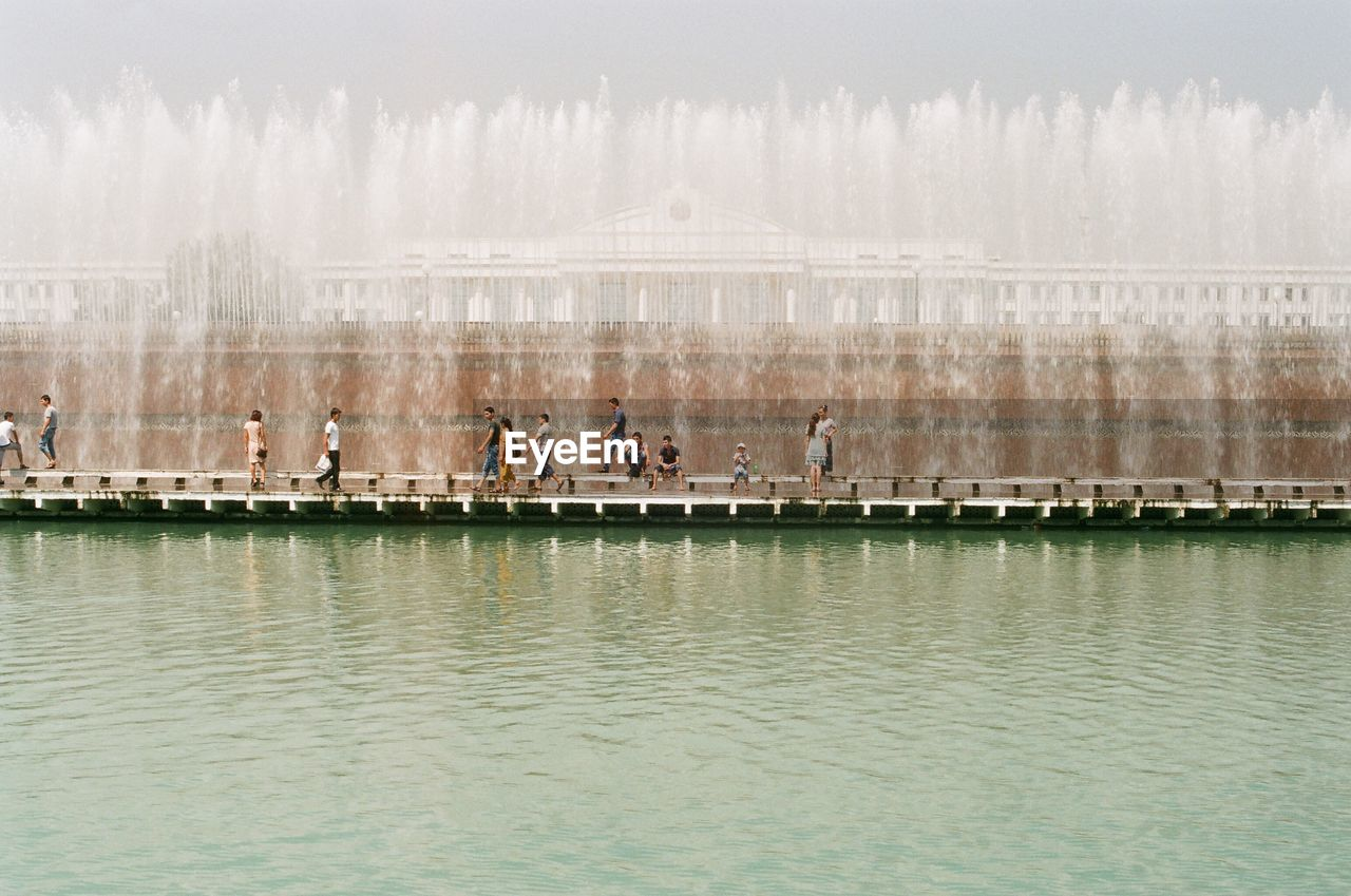 water, real people, building exterior, outdoors, built structure, day, leisure activity, medium group of people, waterfront, architecture, men, lifestyles, women, travel destinations, fog, sky, nature, city, young adult, people