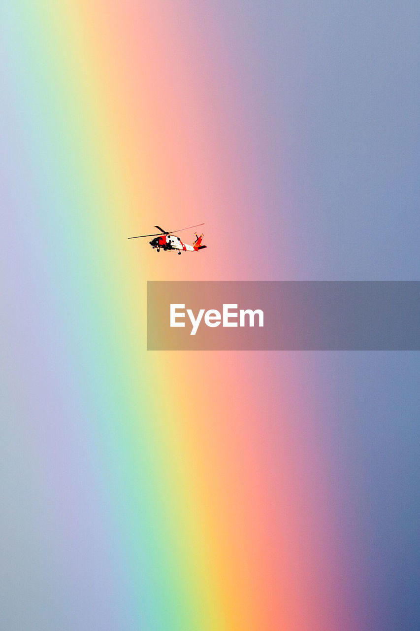 Low Angle View Of Helicopter Flying Against Rainbow
