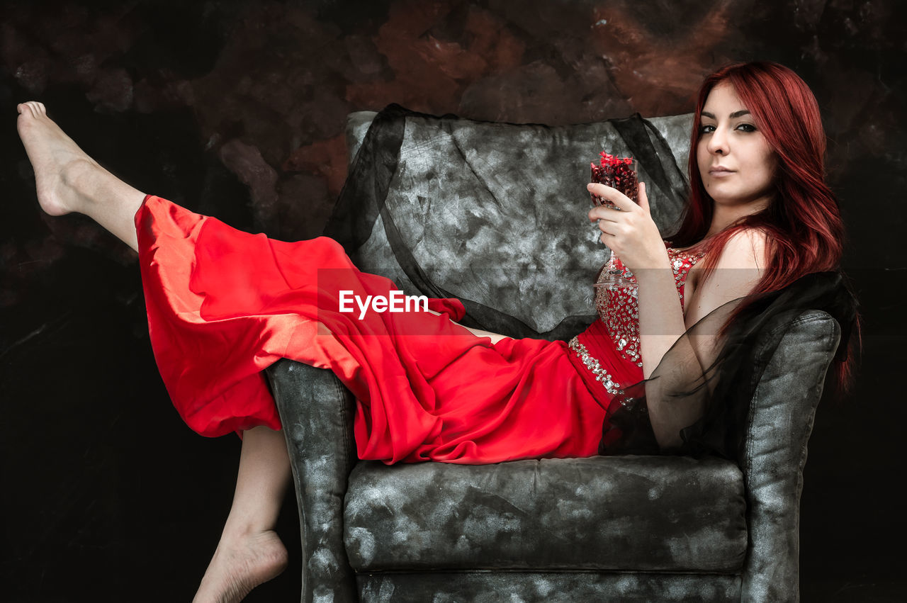 sitting, one person, young adult, red, young women, real people, lifestyles, full length, leisure activity, indoors, holding, three quarter length, adult, clothing, casual clothing, women, fashion, seat, beautiful woman, hairstyle