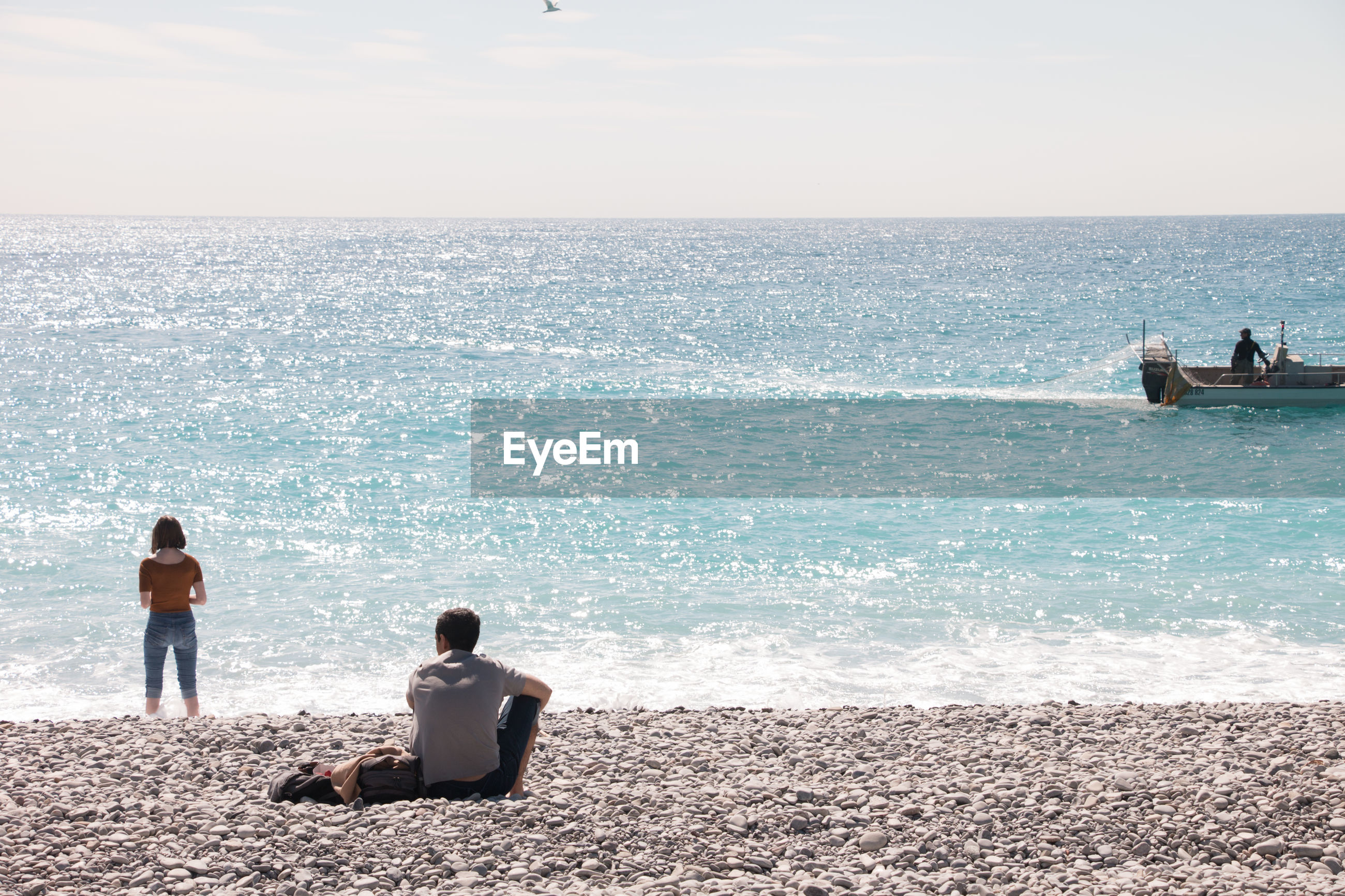 REAR VIEW OF PEOPLE LOOKING AT SEA