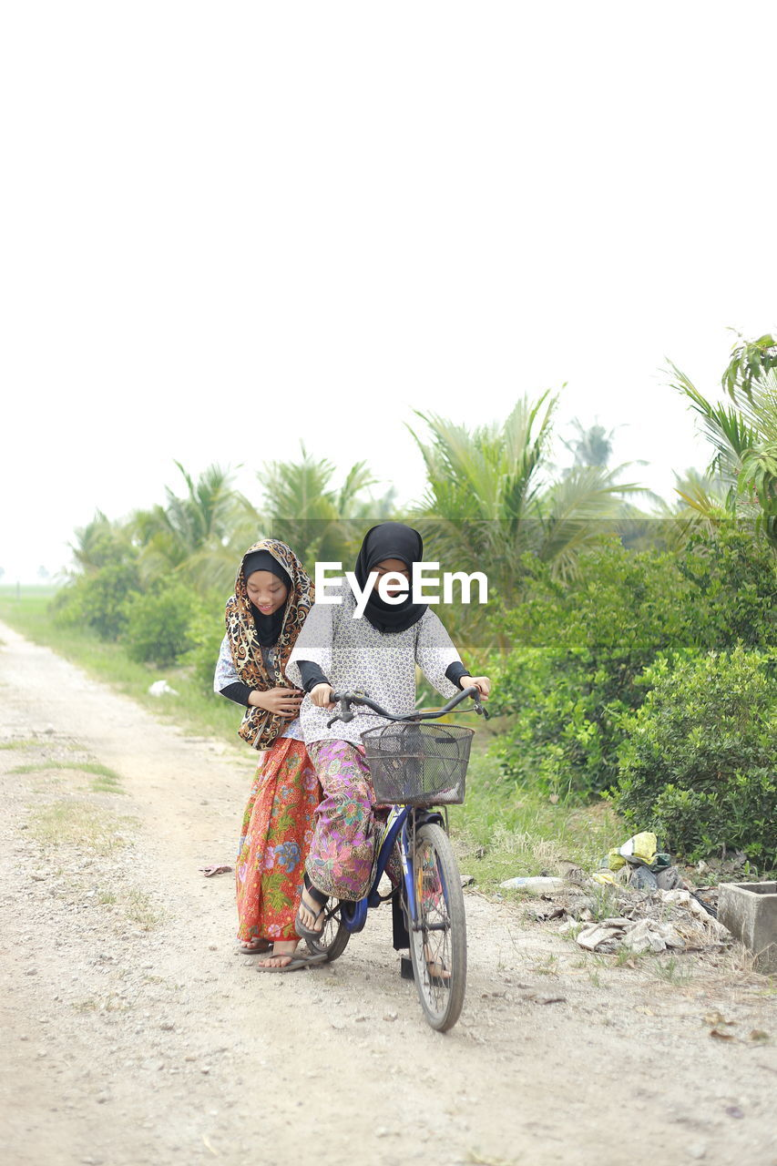 Girl with sister riding bicycle on dirt road
