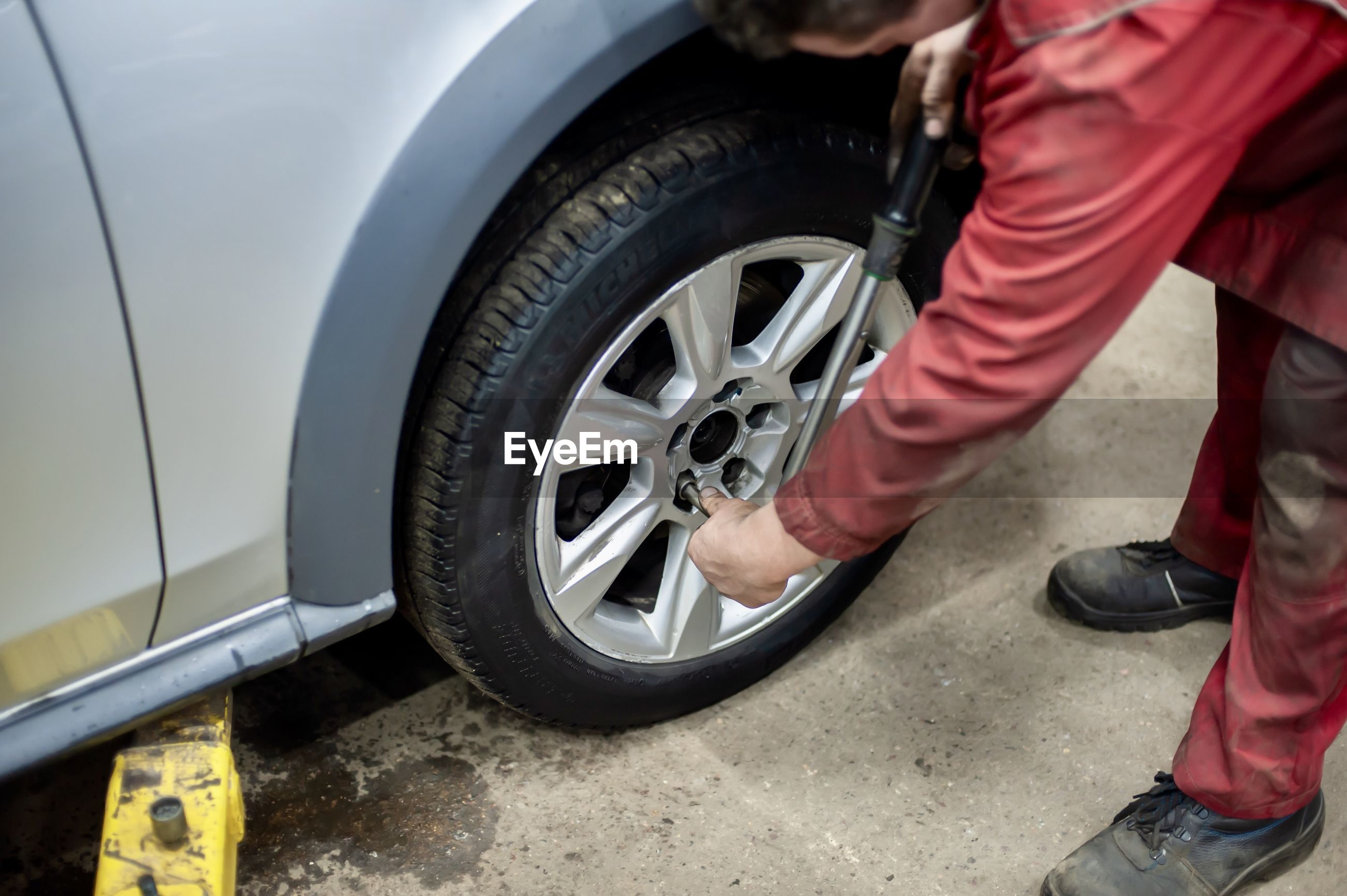LOW SECTION OF MAN WORKING ON CAR