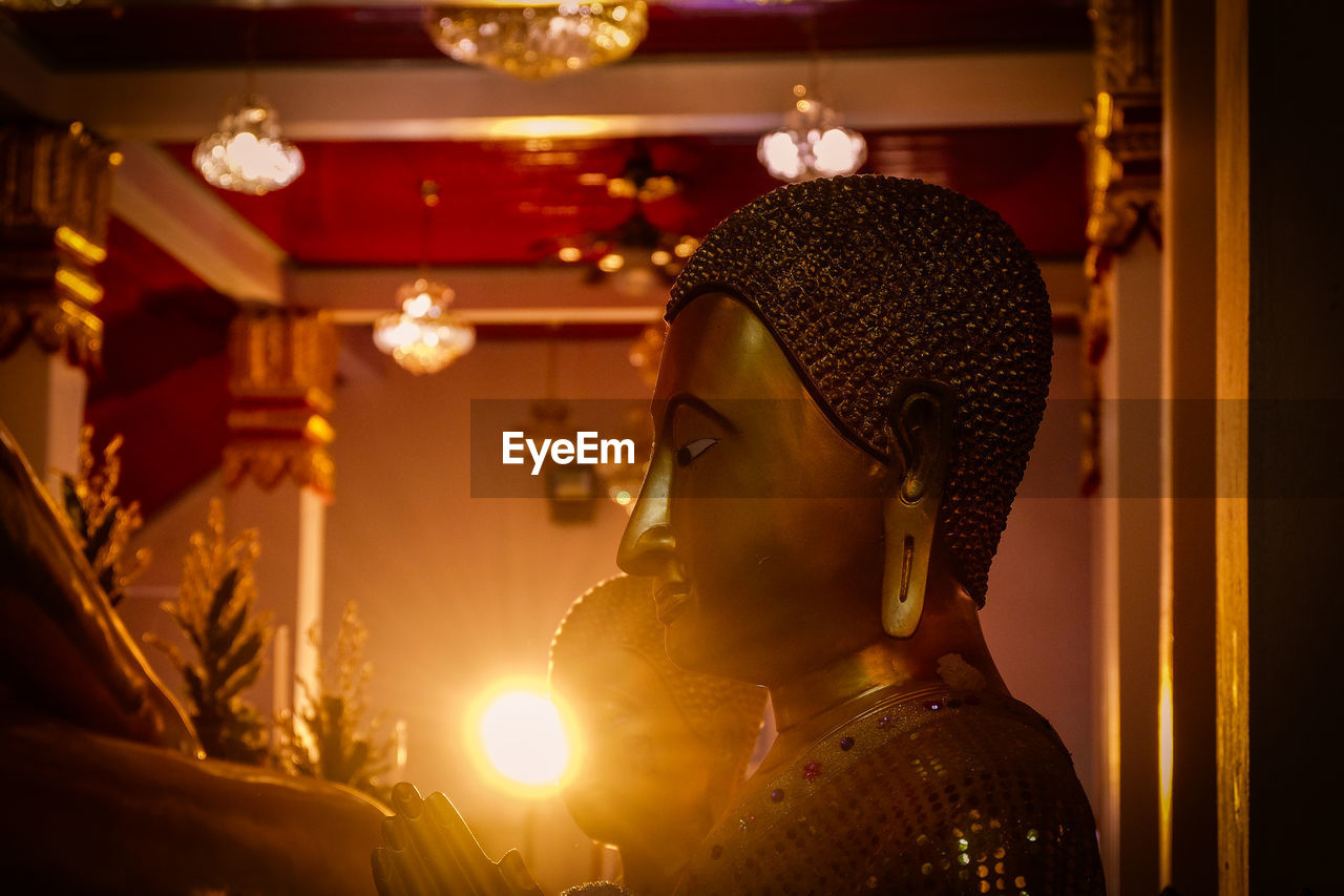 illuminated, indoors, headshot, lighting equipment, sculpture, one person, statue, portrait, human representation, focus on foreground, representation, clothing, arts culture and entertainment, gold colored, real people, side view, art and craft, religion, architecture, light
