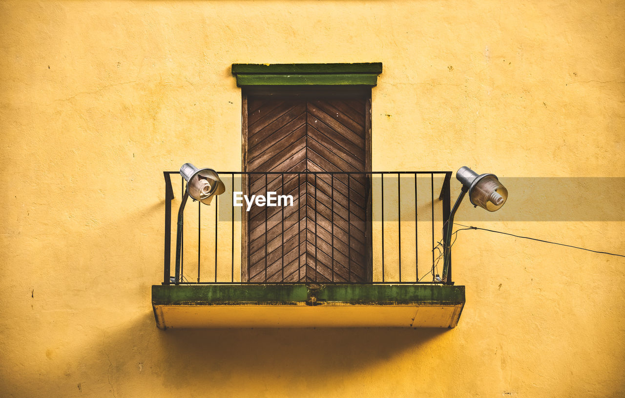 built structure, architecture, wall - building feature, no people, metal, building exterior, day, yellow, window, door, outdoors, entrance, security, closed, building, protection, wood - material, safety, low angle view